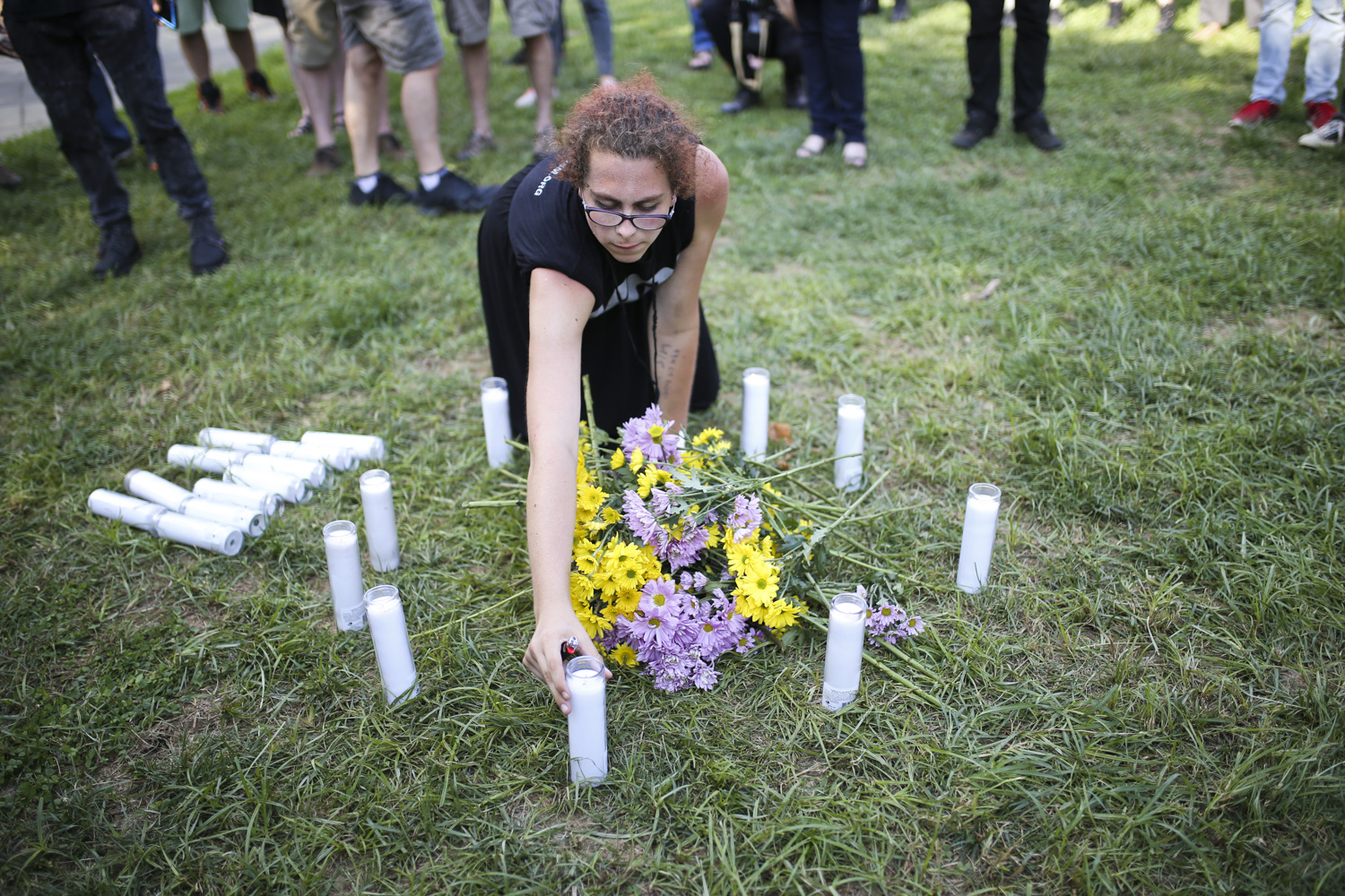 A woman lays candles in the grass during a vigil for Heather Heyer who was killed during Saturday's protests in Charlottesville, at McGuffey Park in Charlottesville on Saturday, August 12, 2017. [Scott P. Yates/progress-index.com]
