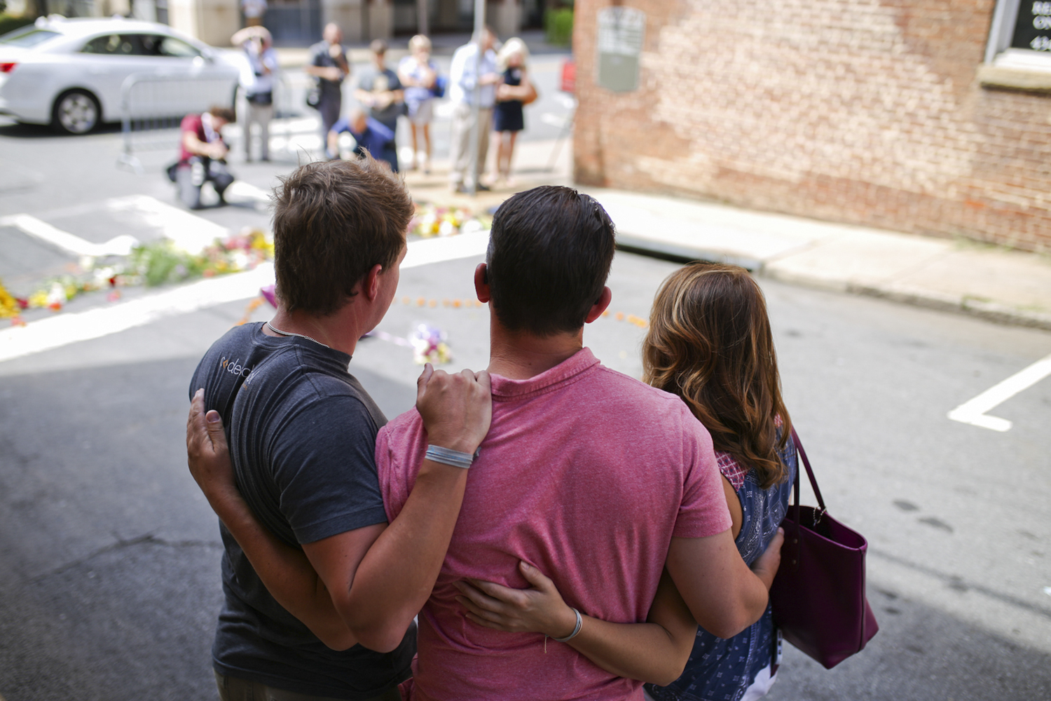Charlottesville residents, from left, David Brear, Kerry Rock and Colleen Todd hug at the street memorial for the victim of Saturday's terrorist attack on counter protesters in Charlottesville, Va., on Sunday, August 13, 2017. [Scott P. Yates for The Wall Street Journal]