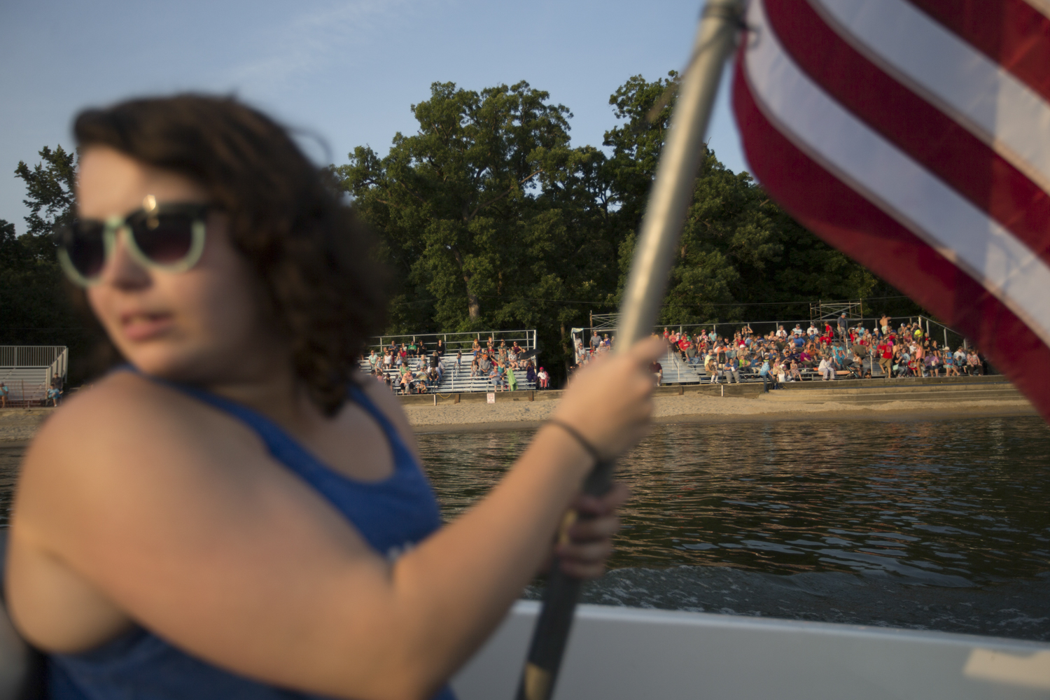 Cassie Fleener, a spotter, holds the American flag during the national anthem prior to a Ski Broncs summer show on Friday, Aug. 3. The boat makes circles in the river in front of the grandstands during the anthem. During the show, Fleener and her teammate, boat driver Ron Anderson, operate a 600 horse power-engine boat that generally pulls the larger group formations. [SCOTT P. YATES/RRSTAR.COM STAFF]