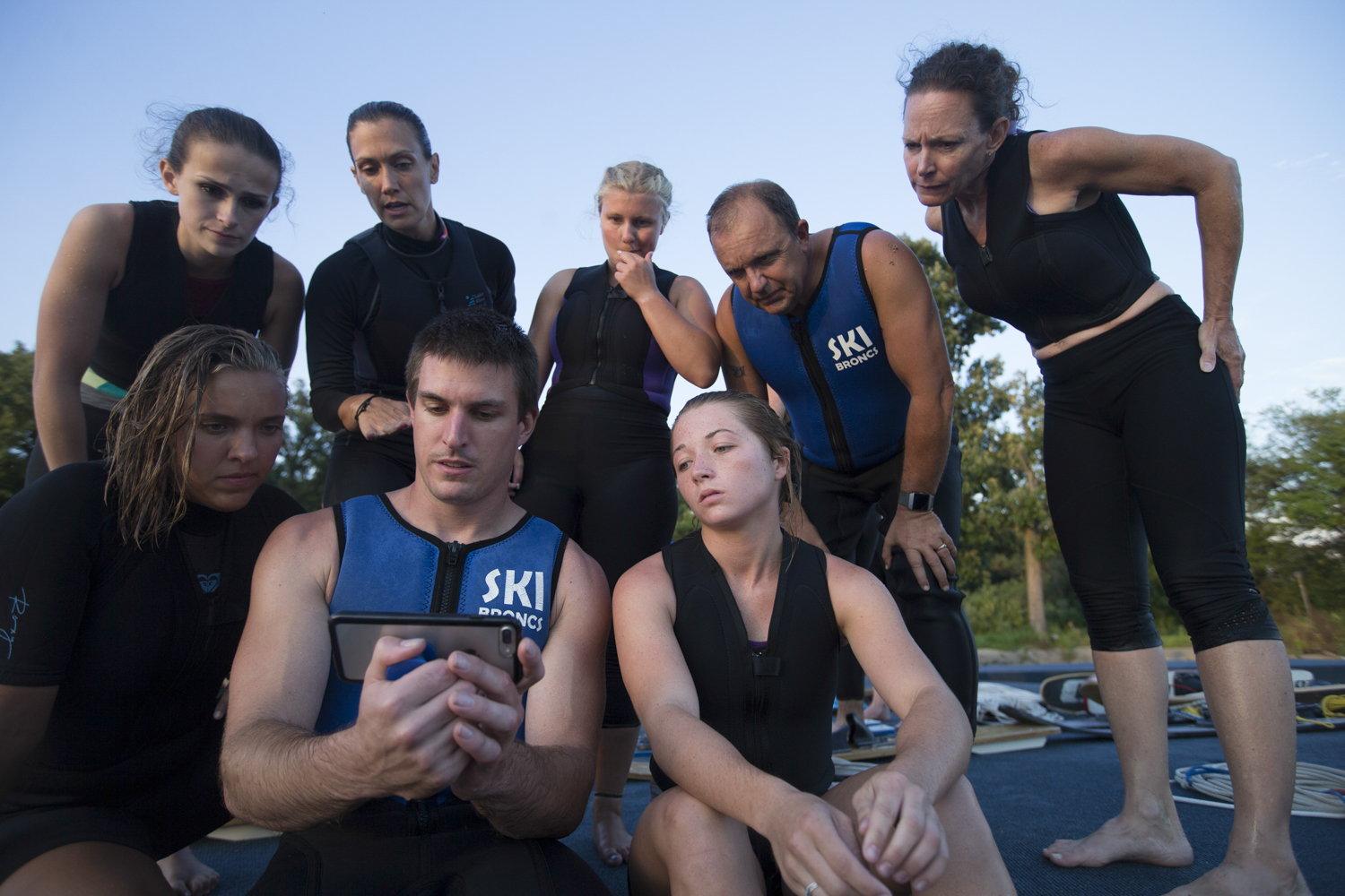 Show director Brandon Seerup, center, and members of the team review a mobile phone video of their last formation while sitting on the edge of the dock on Tuesday, July 31, 2018, at Shorewood Park in Loves Park. [SCOTT P. YATES/RRSTAR.COM STAFF]