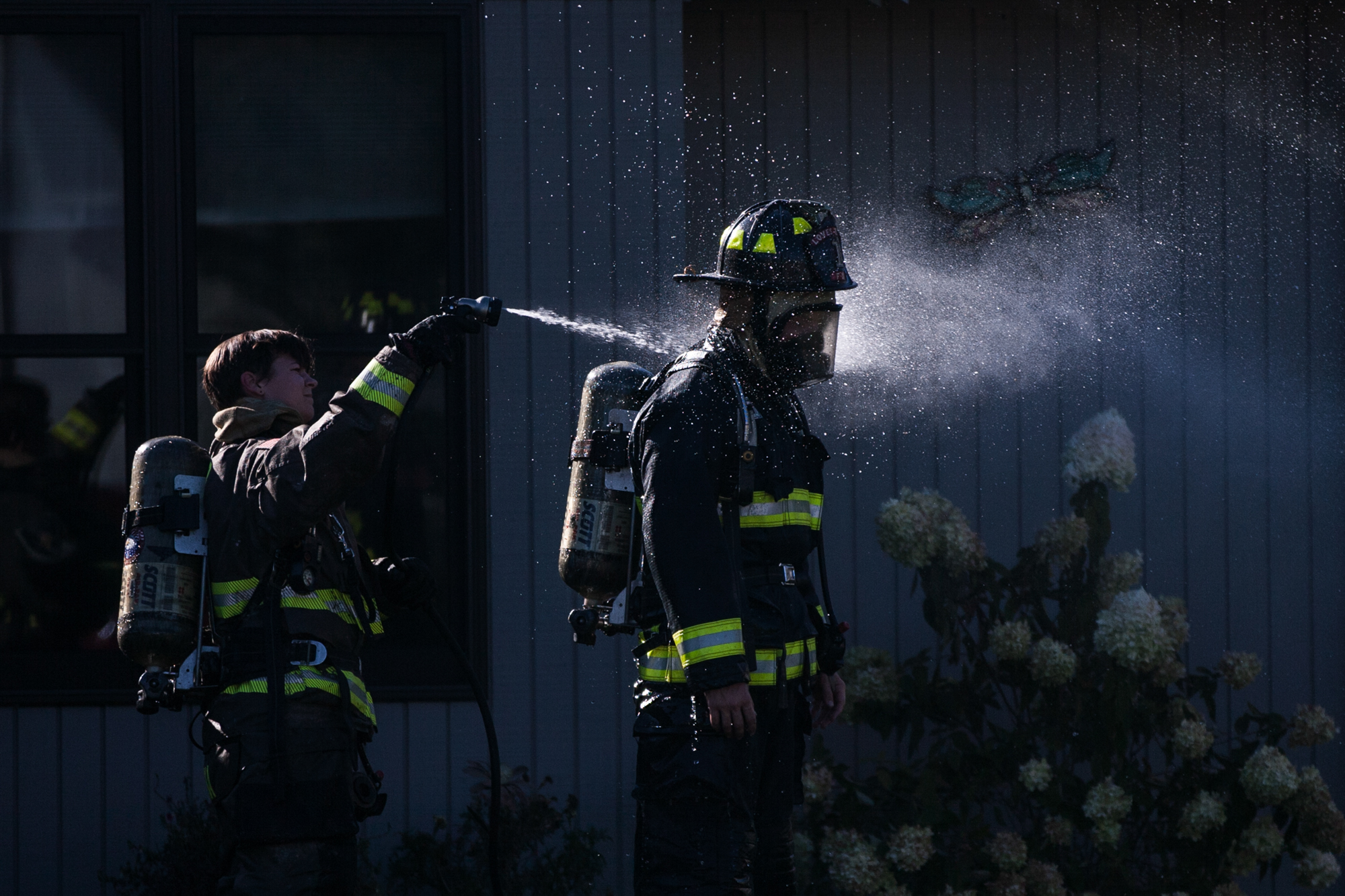 Fire departments from Loves Park rinse of equipment after exposure to gas and loose housing insulation at the scene of a house fire on Tuesday, Sept. 11, 2018, at the 4300 block of Kingsbury Drive in Loves Park. [SCOTT P. YATES/RRSTAR.COM STAFF]