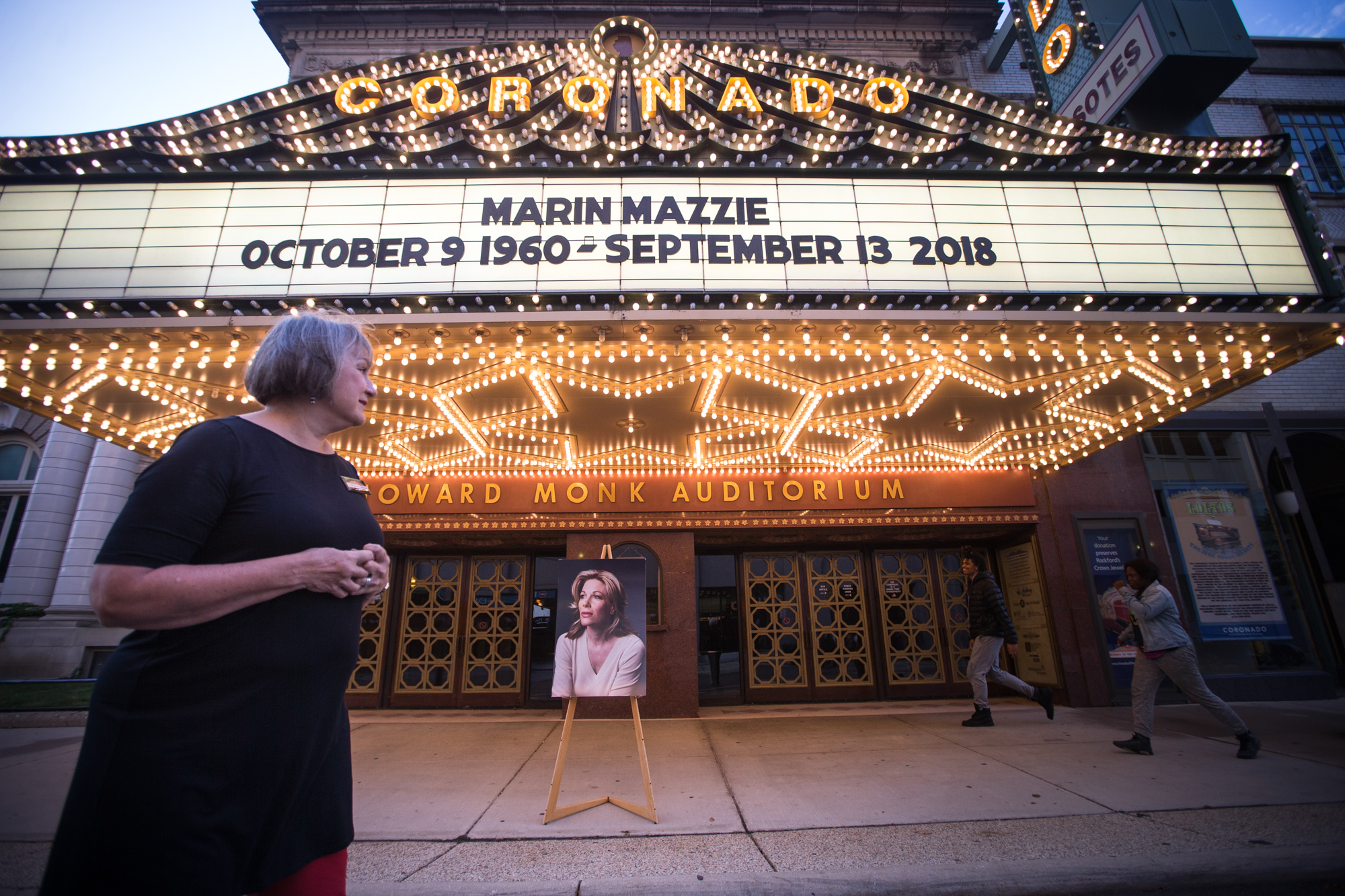Mary Ann Smith of Rockford, the president of the Friends of the Coronado, takes a quiet moment near a portrait of the late Marin Mazzie, a Rockford native and Broadway theater star and who died September 13, on Wednesday, Sept. 19, 2018, at the Coronado Performing Arts Center in Rockford. About a dozen people gathered outside the theater to witness the marque lights shut off for one minute in Mazzie's honor. [SCOTT P. YATES/RRSTAR.COM STAFF]