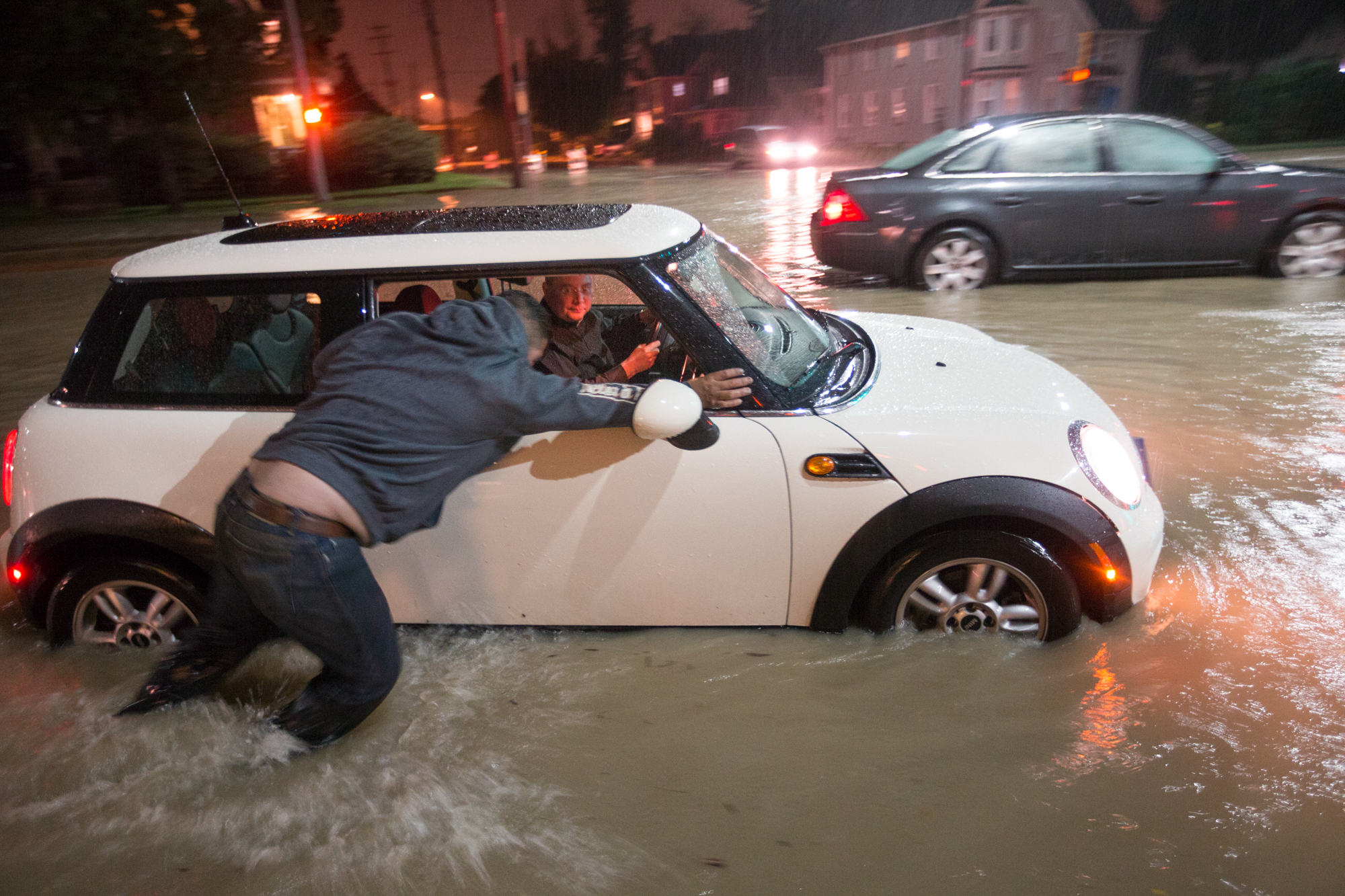 Mariano Cuevas pushes Ricard Hernandez's disabled car out of the flooded street on Tuesday, Aug. 28, 2018, at the intersection of Charles and 9th Streets in Rockford. Hernandez's car later restarted and he drove away. [SCOTT P. YATES/RRSTAR.COM STAFF]