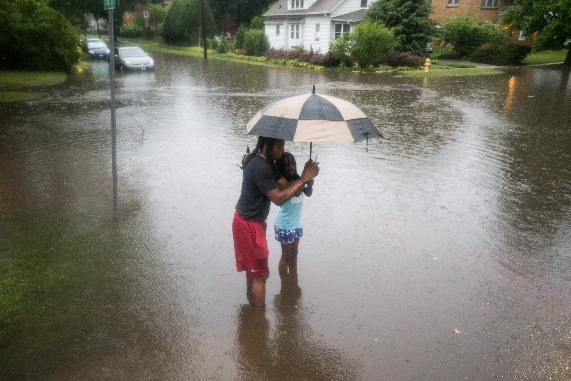 Matt Simpson, left, and his niece, Nikyia Marzette, pause from a walk to take pictures of ducks swimming in the flooded street on Monday, June 18, 2018, at the intersection of Van Wie Avenue and Hancock Street in Rockford. Heavy rains flooded parts of the city and Simpson was out checking for water damage at several residences he owns in the neighborhood. [SCOTT P. YATES/RRSTAR.COM STAFF]