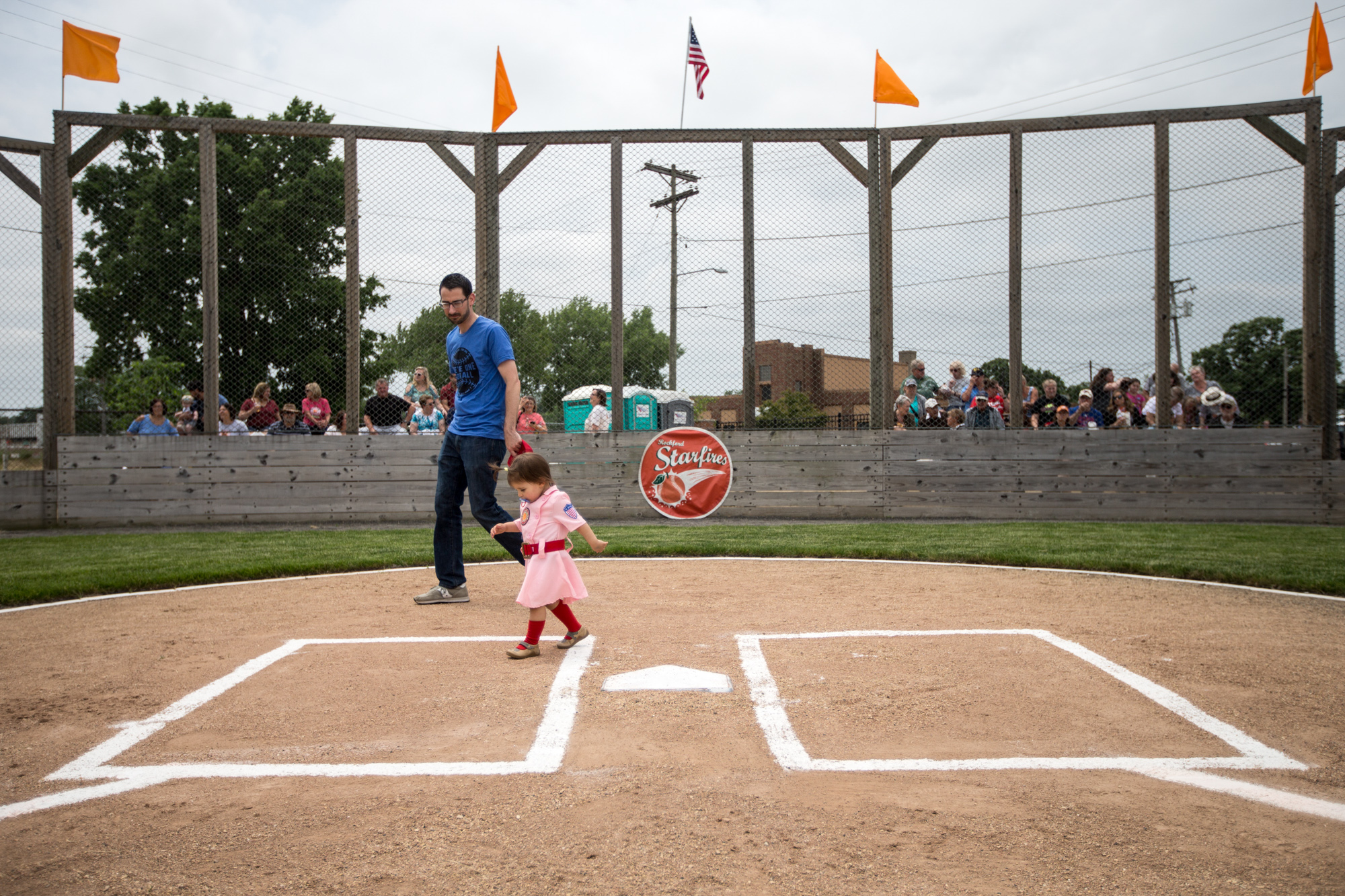 Rockford Mayor Tom McNamara and his daughter Olympia Rose walk across home plate before an exhibition game on Saturday, June 2, 2018, at Beyer Stadium in Rockford. McNamara threw out the first pitch of the game. [SCOTT P. YATES/RRSTAR.COM STAFF]