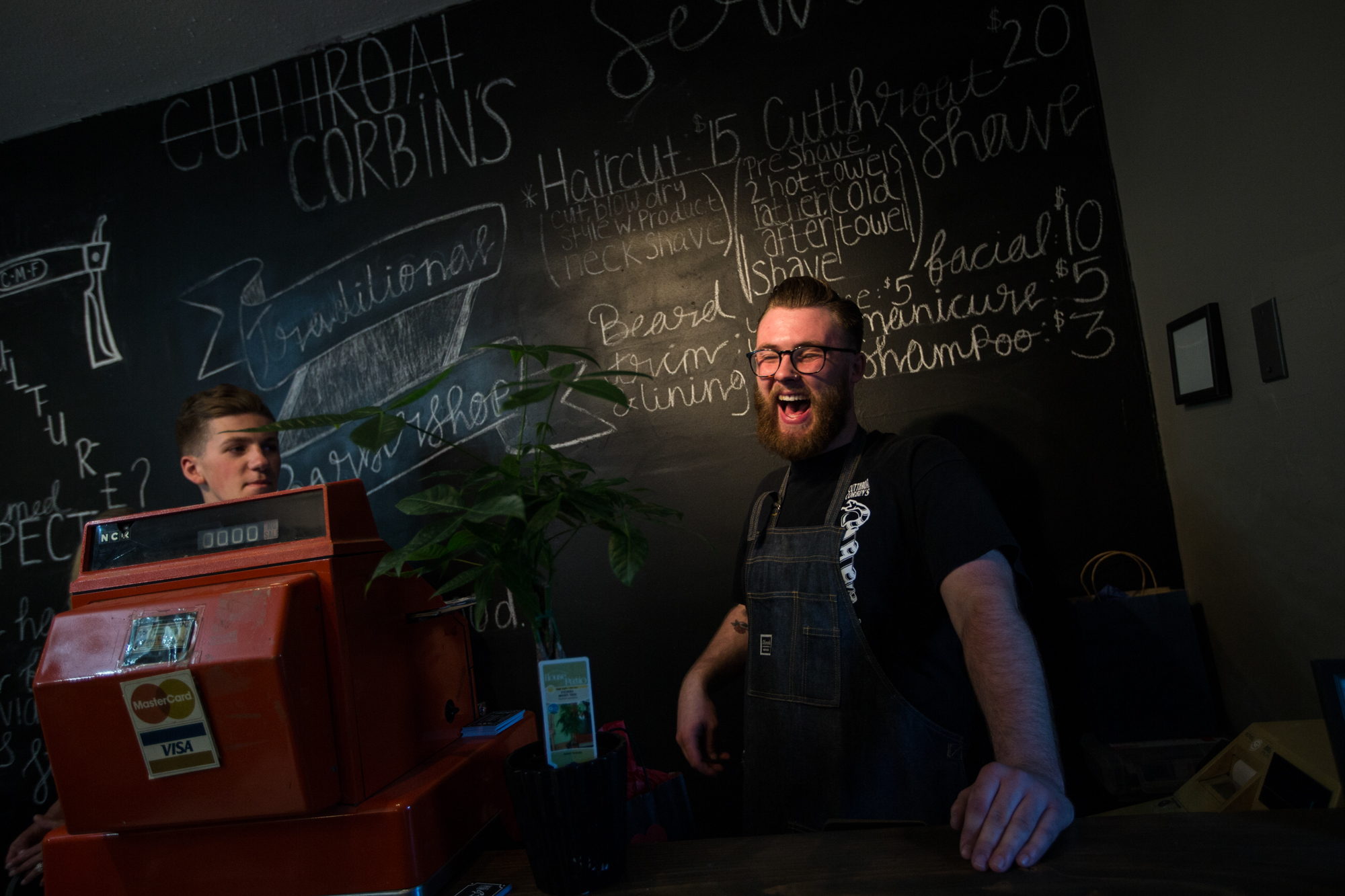 Corbin Fincham, 19, laughs with a friend at the cashier desk during the grand opening of his new barbershop on Friday, June 1, 2018, at Cutthroat Corbin's Barber Shop in Rockton. [SCOTT P. YATES/RRSTAR.COM STAFF]