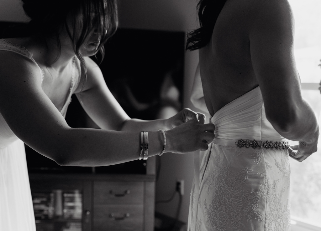 Detail image of bride getting ready. Sister tying brides dress.