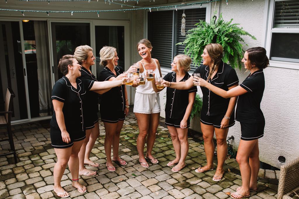 Happy bride in bride pajamas with bridesmaids in matching black pajamas toasting champagne.