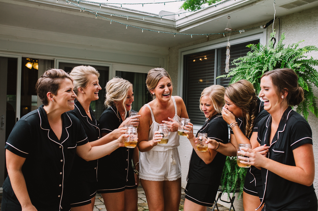 Bride and bridesmaids in matching pajamas laughing hysterically while getting ready for the wedding at Strongwater.