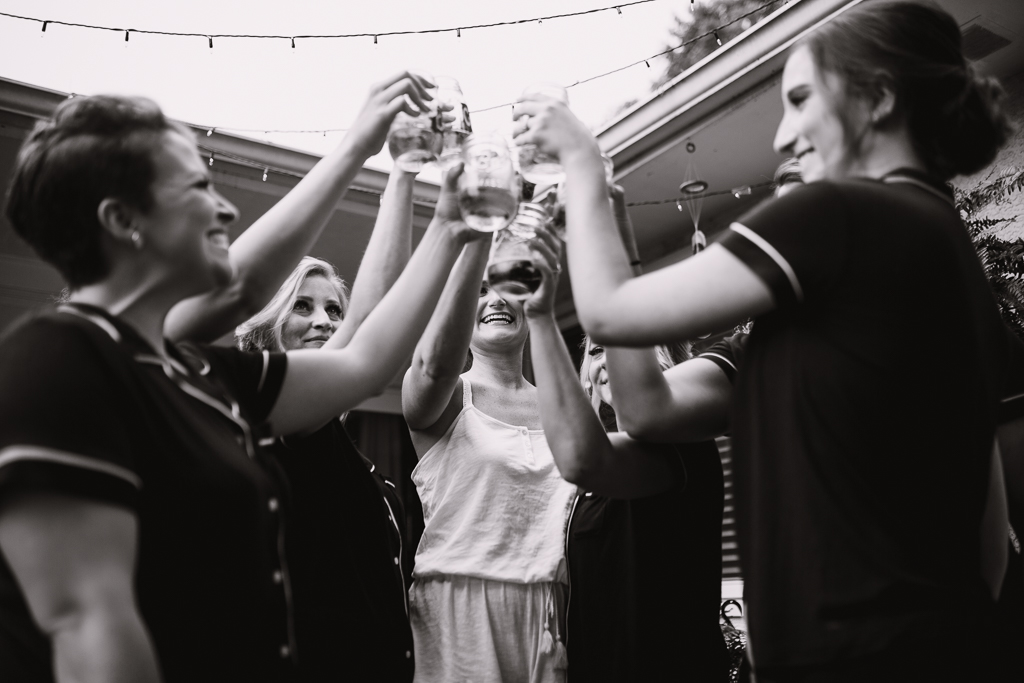 Bride and bridesmaids make a champagne toast while getting ready for wedding at Strongwater. Bride smile is centered in picture and all glasses are raised in the air.