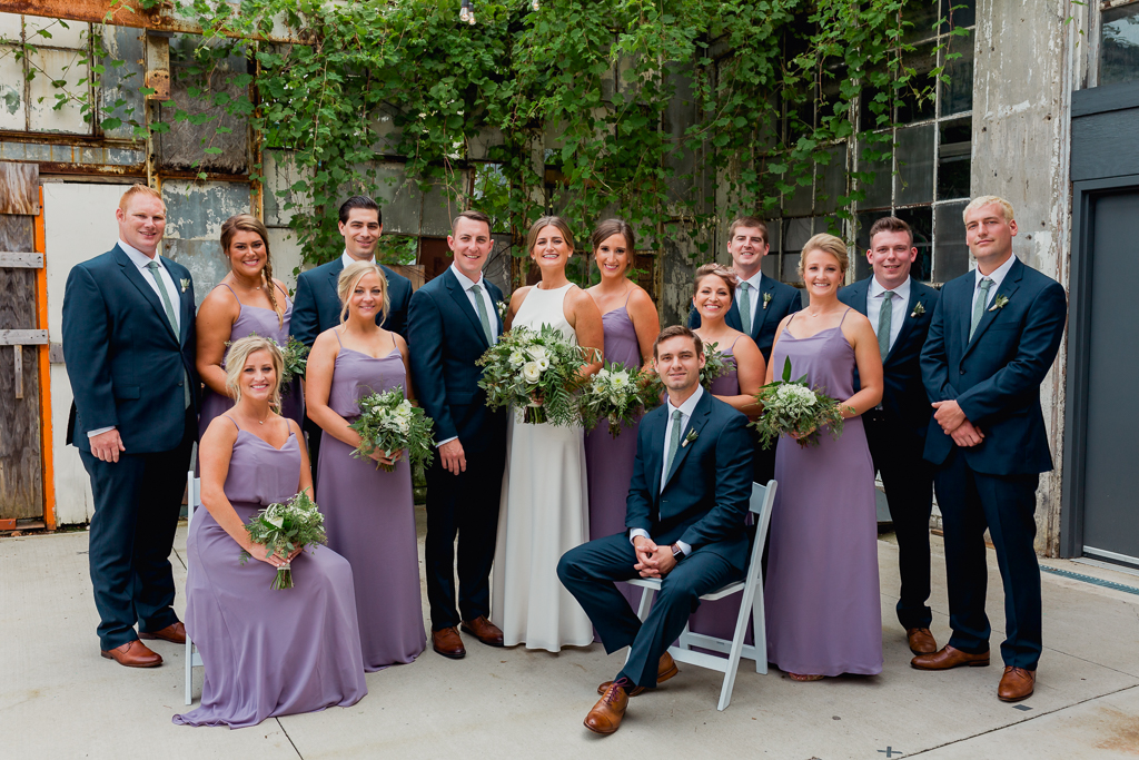 Groomsmen in navy suits and bridesmaids in lavender chiffon gowns. Large bridal party posed both standing and sitting while outdoors at a wedding at Strongwater Food and Spirits in Columbus OH.