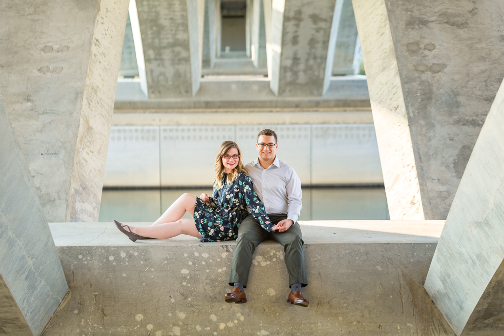 Engaged couple cuddles close under the bridge at the Scioto Mile during their fall engagement session.