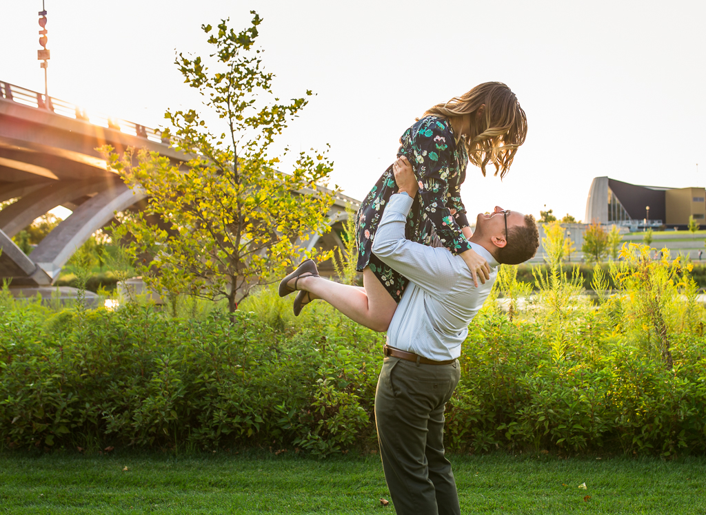 Guy lifts girl off the ground with beautiful greenery and sunset in the background at this Scioto Mile enagagement session.