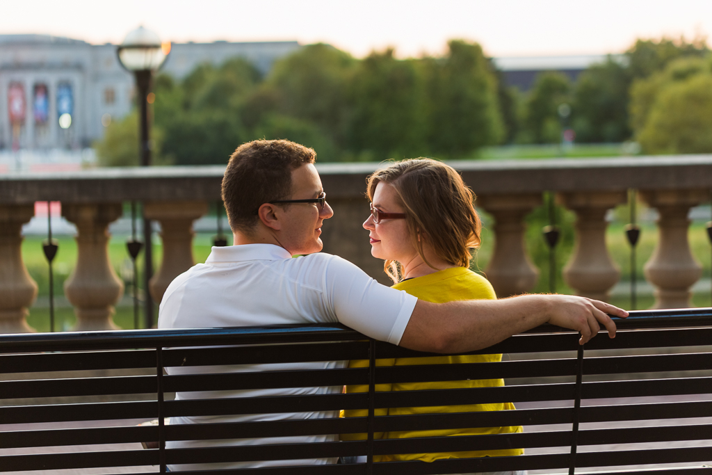 Engaged couple sits on park bench staring into each others eyes while the sunsets over the Scioto Mile and Riverfront after a romantic engagement session.