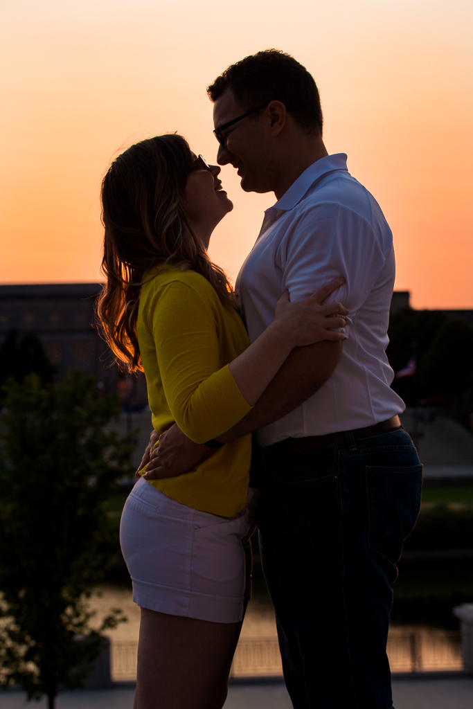 Beautiful orange and peach sunset over the Scioto river and silhouettes a couple embracing after their romantic and fun engagement session at the Riverfront and Scioto Mile.