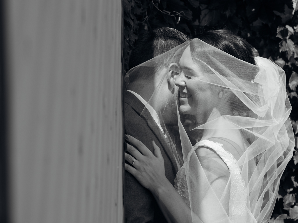 Romantic black and white portrait of bride and groom snuggling under bride's veil.