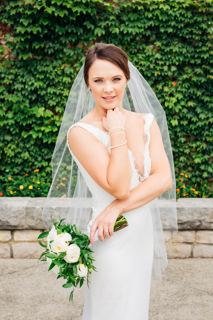 Gorgeous bride looks like she belongs on a magazine cover as she gives a sultry look to the camera. She poses with her bouquet of white peonies in front of a green ivy wall at Northbank Park and Pavilion in Columbus OH.
