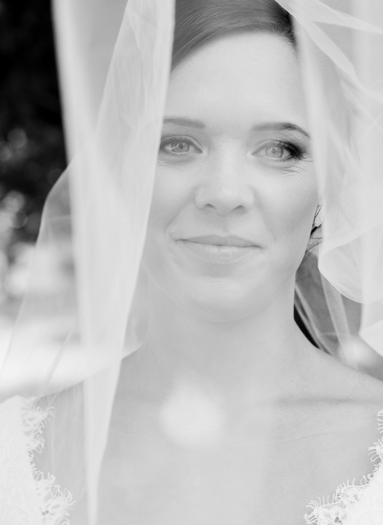 Bride with classic beauty smiles and peeks out from under her veil in this black and white portrait. She is ready to get married at Northbank Park!