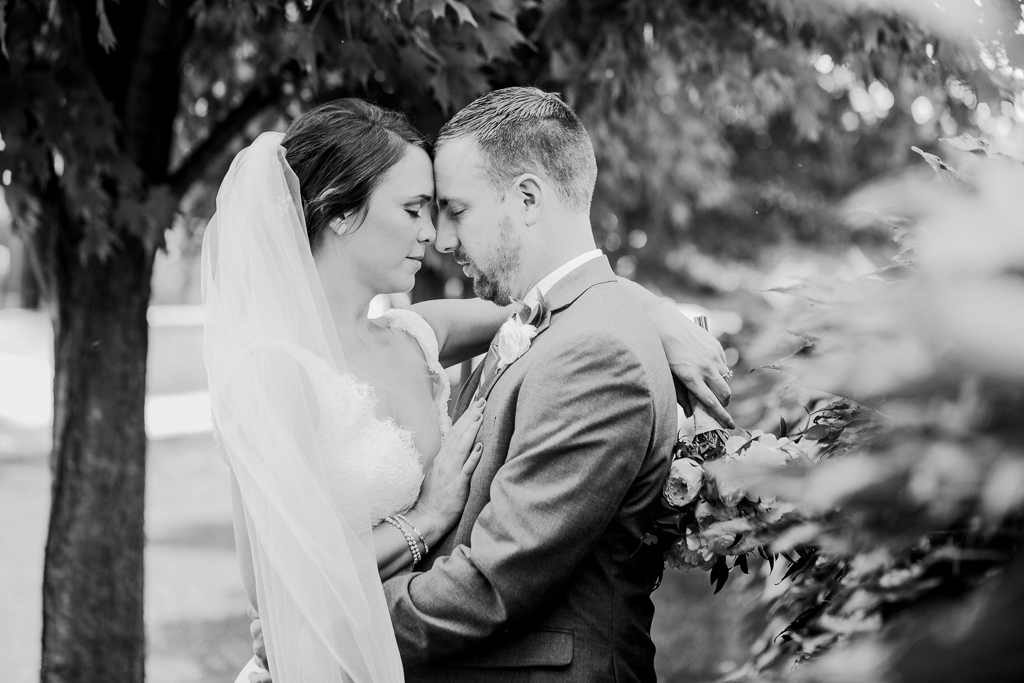 Black and white portrait of bride and groom embracing with closed eyes, surrounded by greenery and trees.