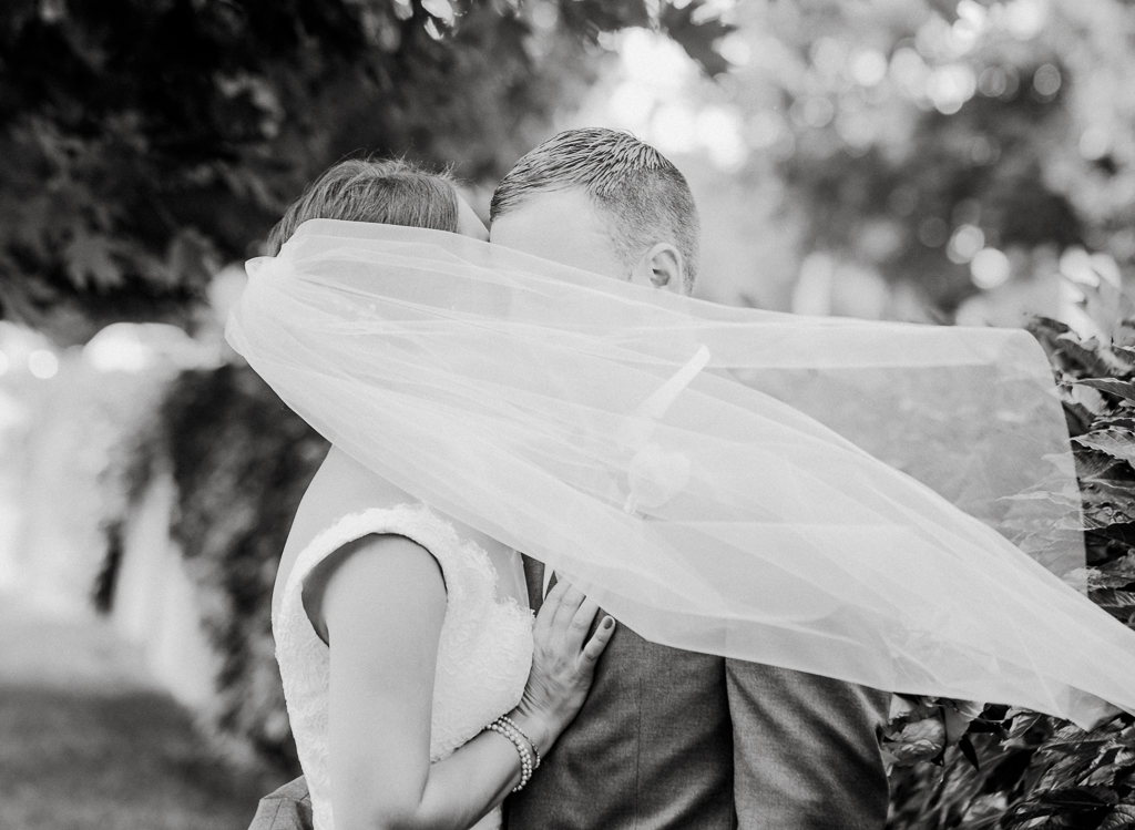 Romantic and mysterious portrait of bride and groom in black and white. A gust of wind blows her veil to obstruct their faces while they kiss before their wedding at Northbank Park and Pavilion in Columbus OH.
