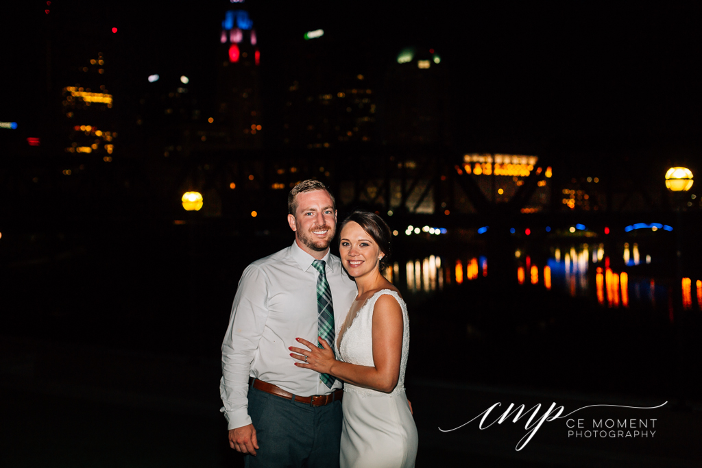 Bride and groom pose in front of Columbus skyline at night after their Northbank park wedding reception in Columbus OH. The night lights in the Columbus skyline reflect on the Scioto river.