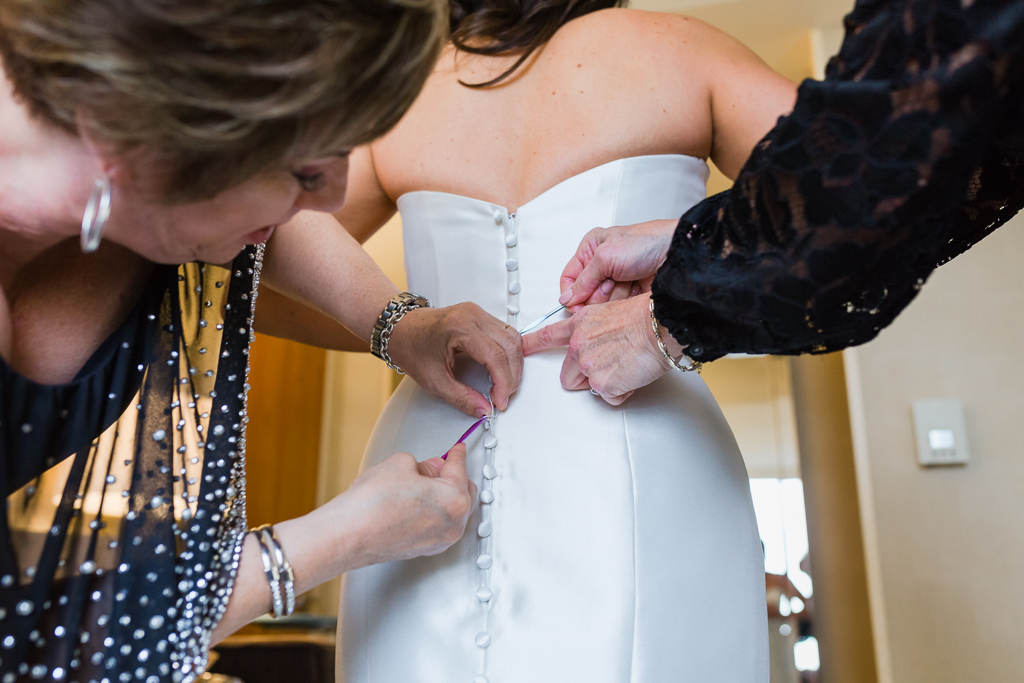 In a lovely suite at the Radisson Hotel in downtown Columbus, OH the bride's mom and step mom work together to fasten each button on her gown