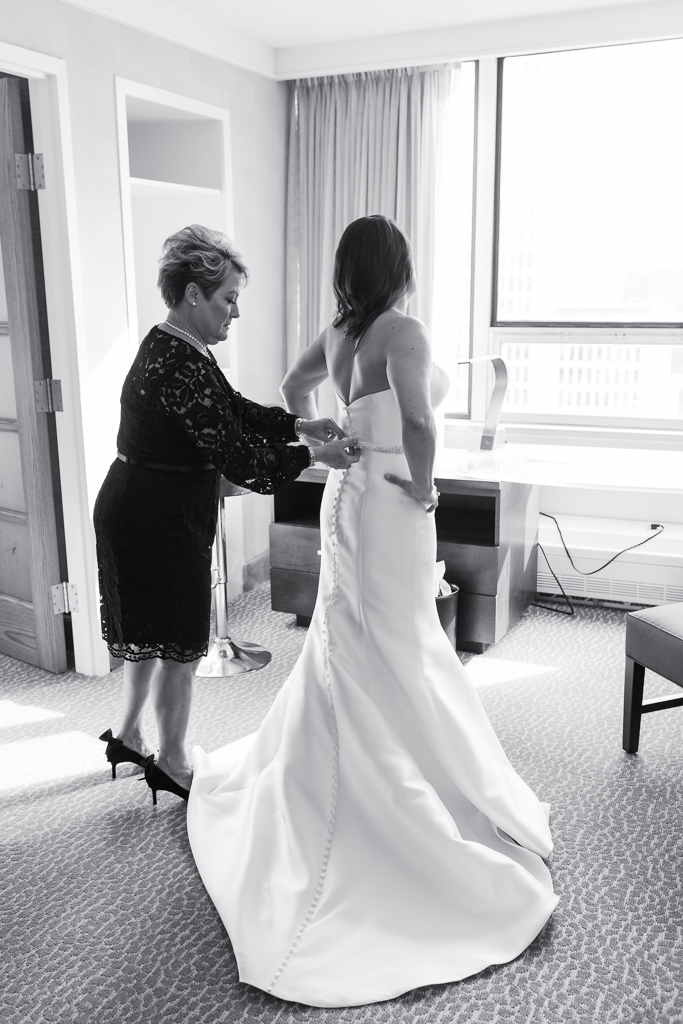 Bride wears long satin gown with full button back detail as she gets ready for her wedding at Via Vecchia in Columbus OH
