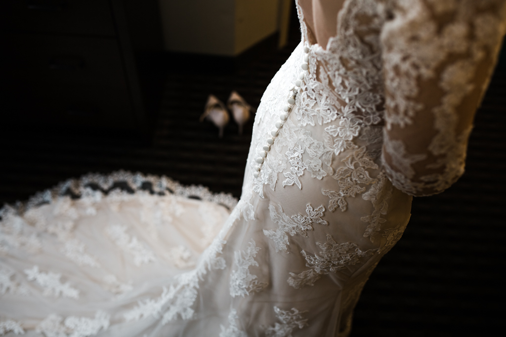 Button detail on back of  fitted, long sleeved, lace Morilee wedding gown.