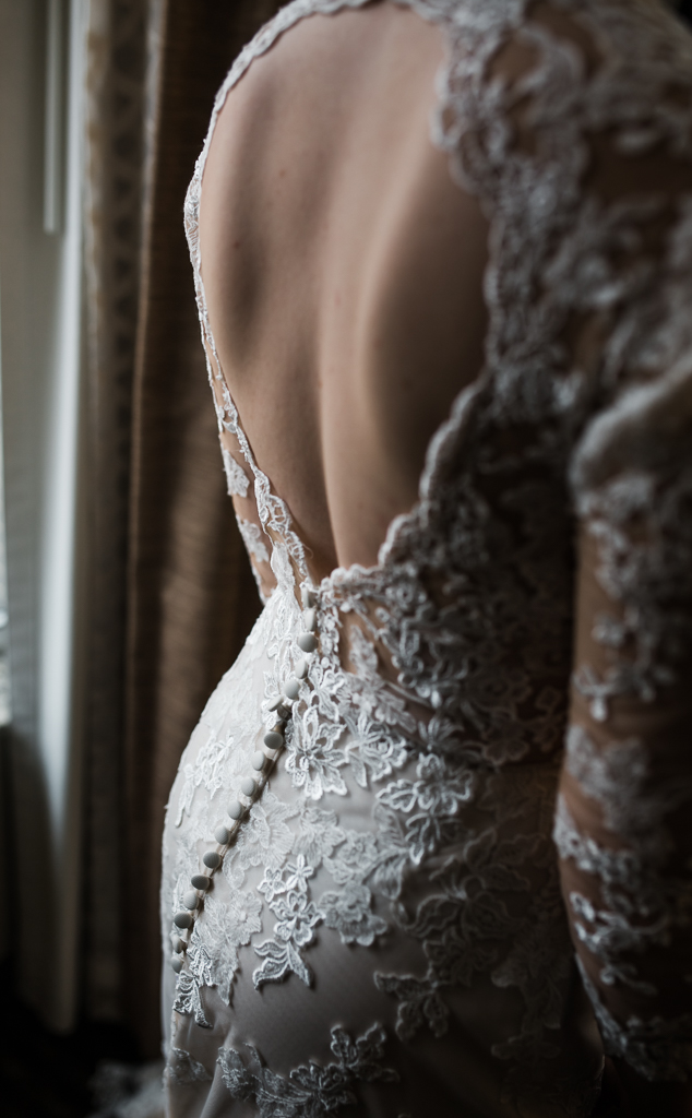 Details of  open back, long sleeved, lace Morilee wedding gown.