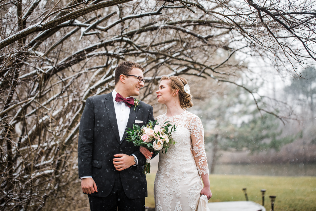 Snowing on Bride and groom gaze as they gaze each other and smile at  Watersedge event center in Hilliard OH.