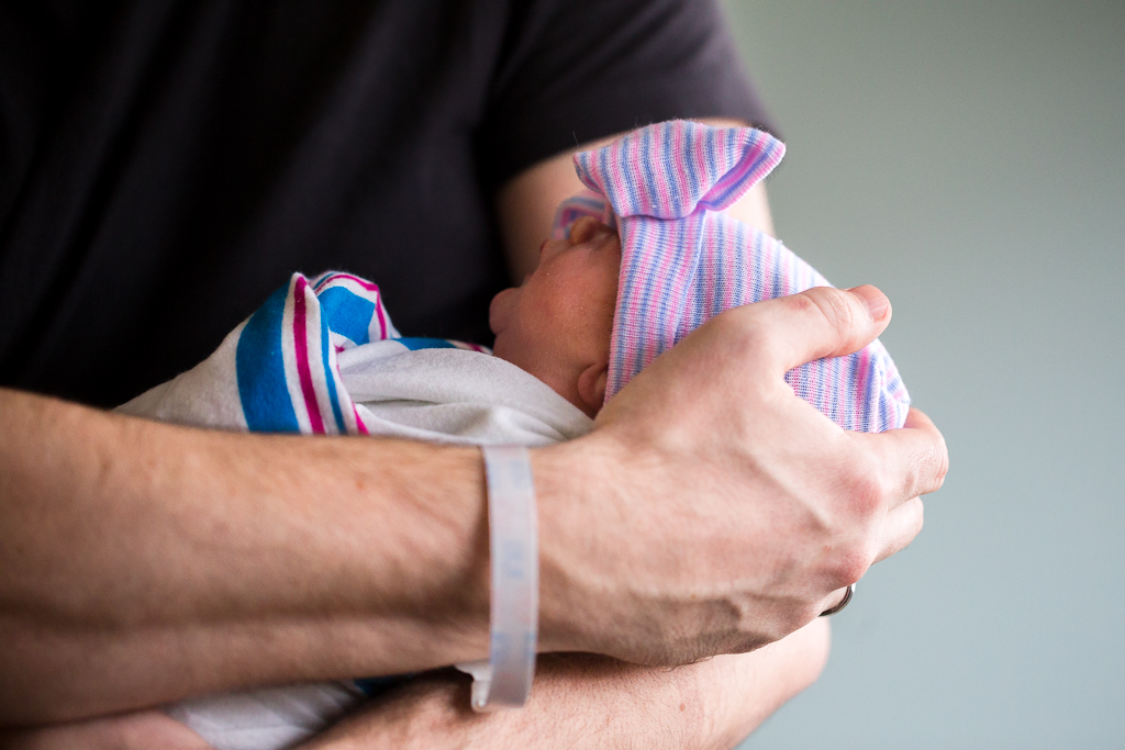 Dad holds his newborn daughter for the first time in the hospital during birth photography session in Columbus Ohio.