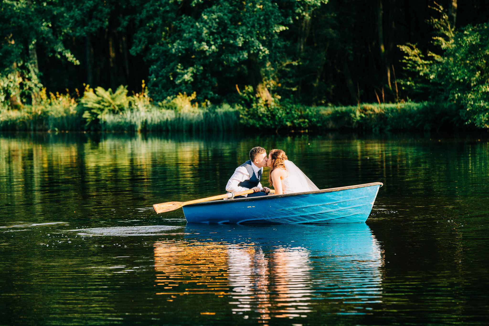 bride and groom kissing on a blue row boat whilst on the lake at Browsholme hall and tithe barn