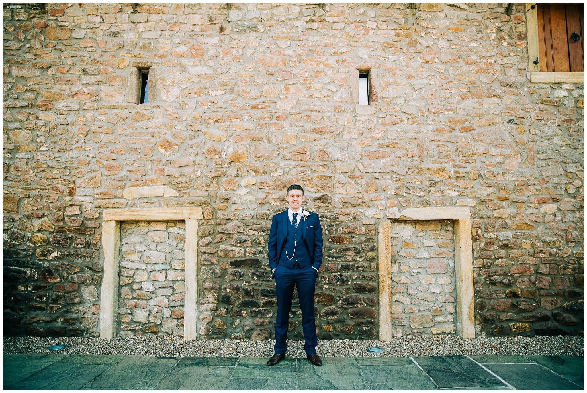 groom stood again stone wall of browsholme tithe barn