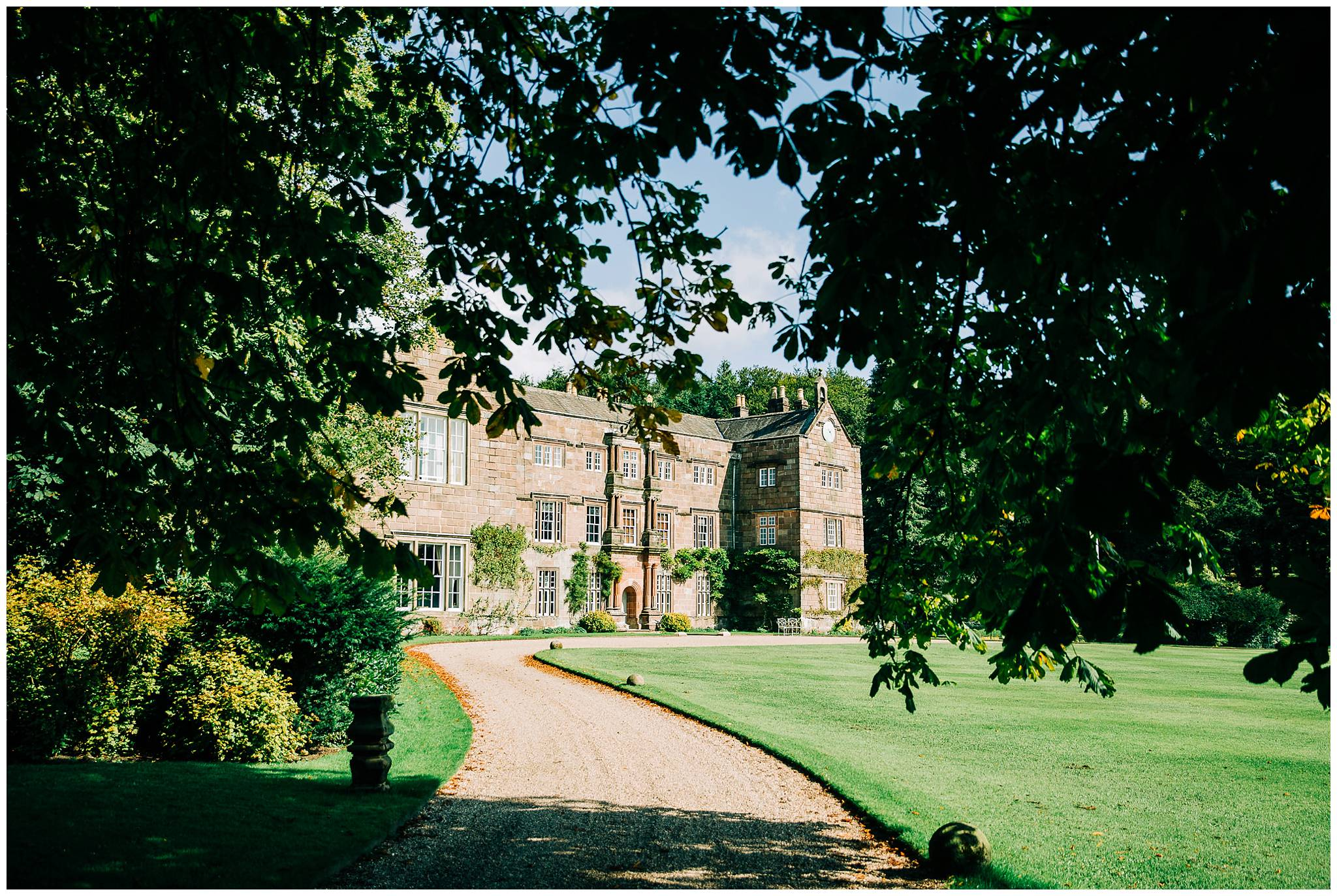 A shaded leafy canopy is framing Browsholme hall which is in the sunny background