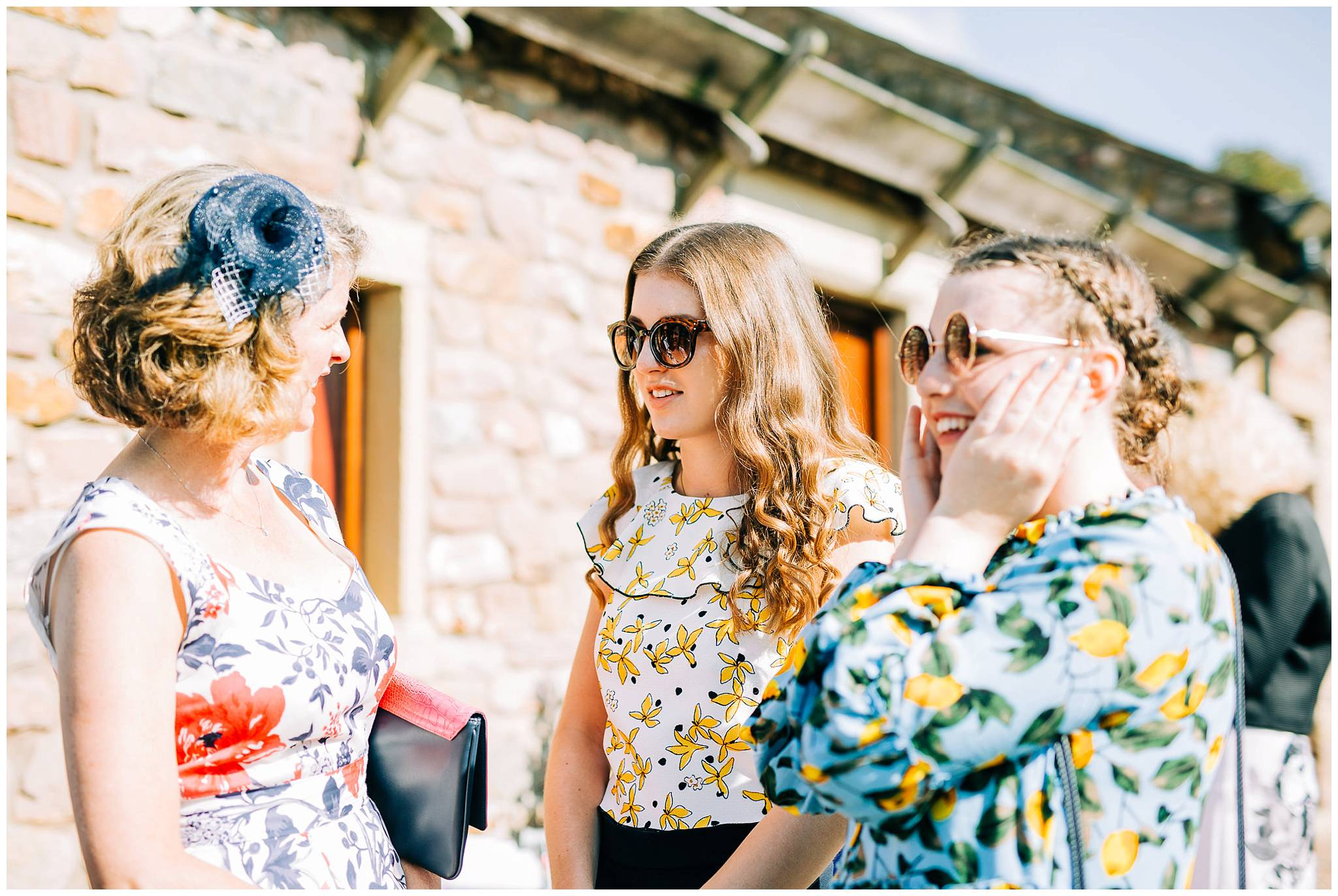 to fashionable girls wearing sunglasses are talking to her mother whislt outside the browsholme barn