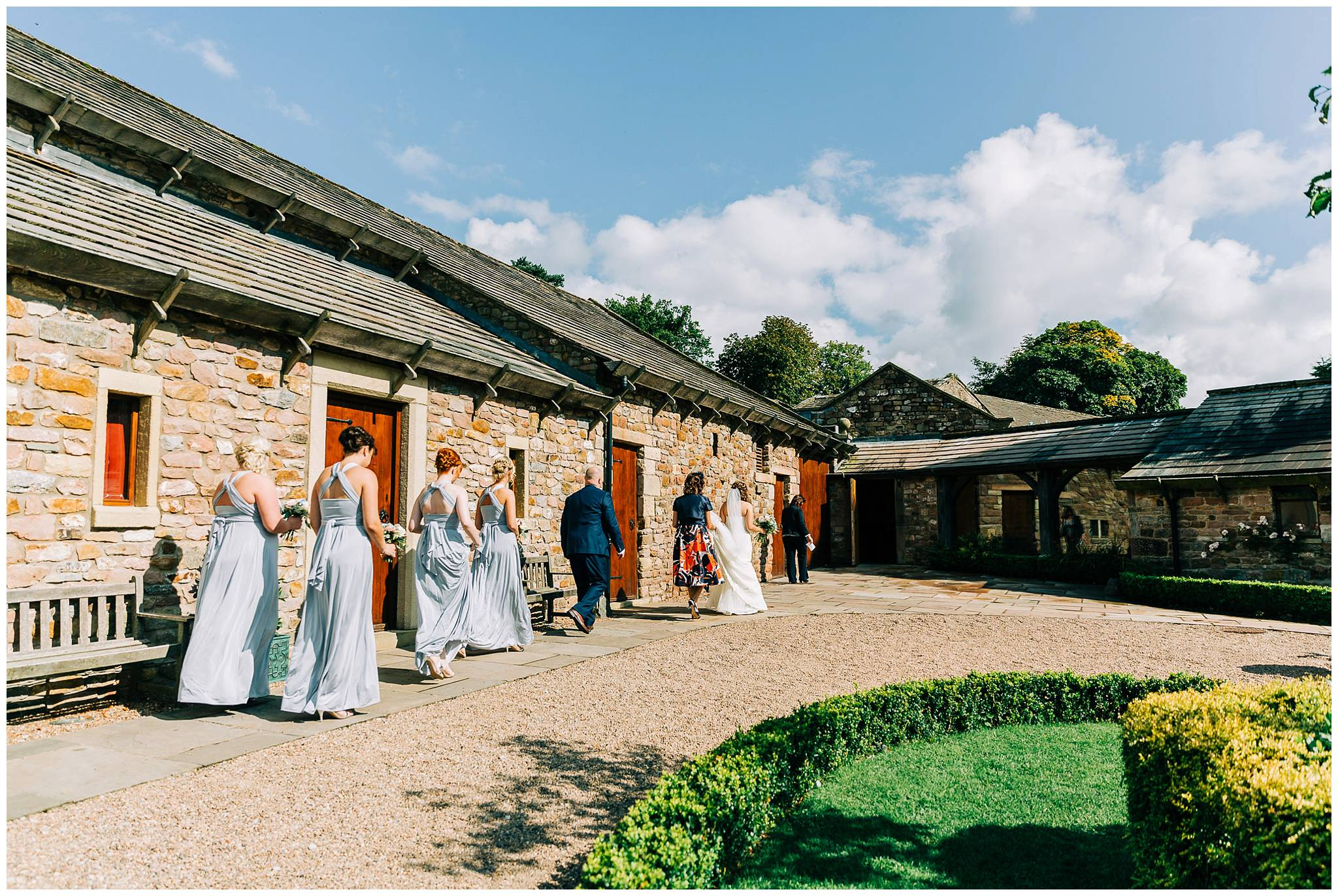 the remainging bridal party outside browsholme tithe barn are now walking in towards the entrance of the barn