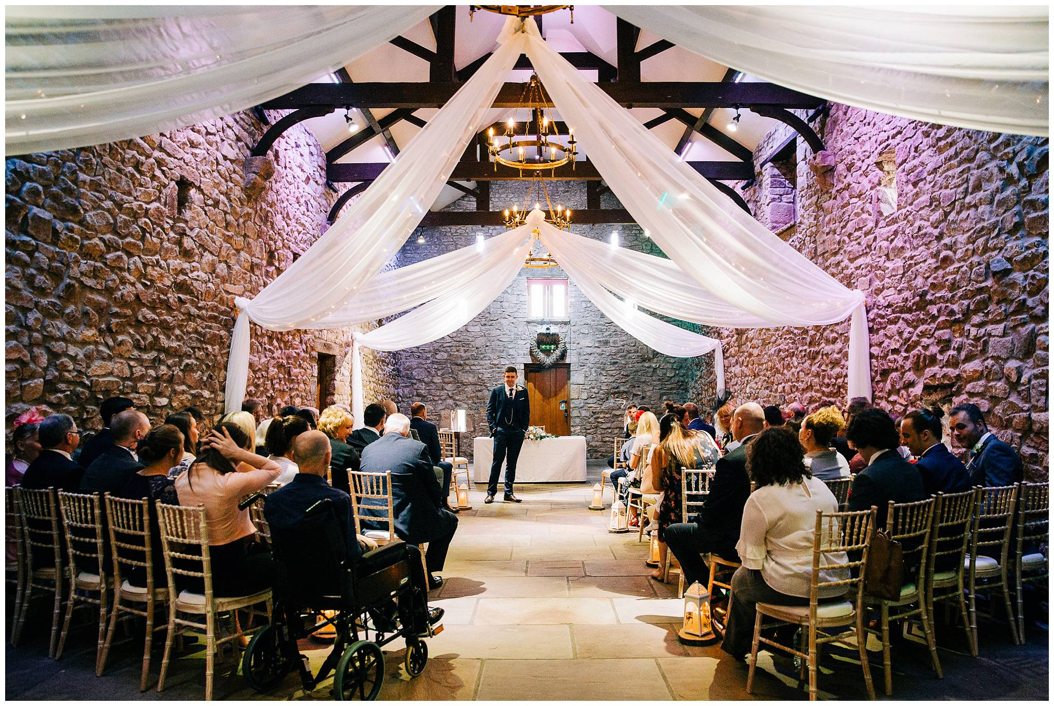browsholme tithe barn is filled with guests and groom waiting for the bride to arrive