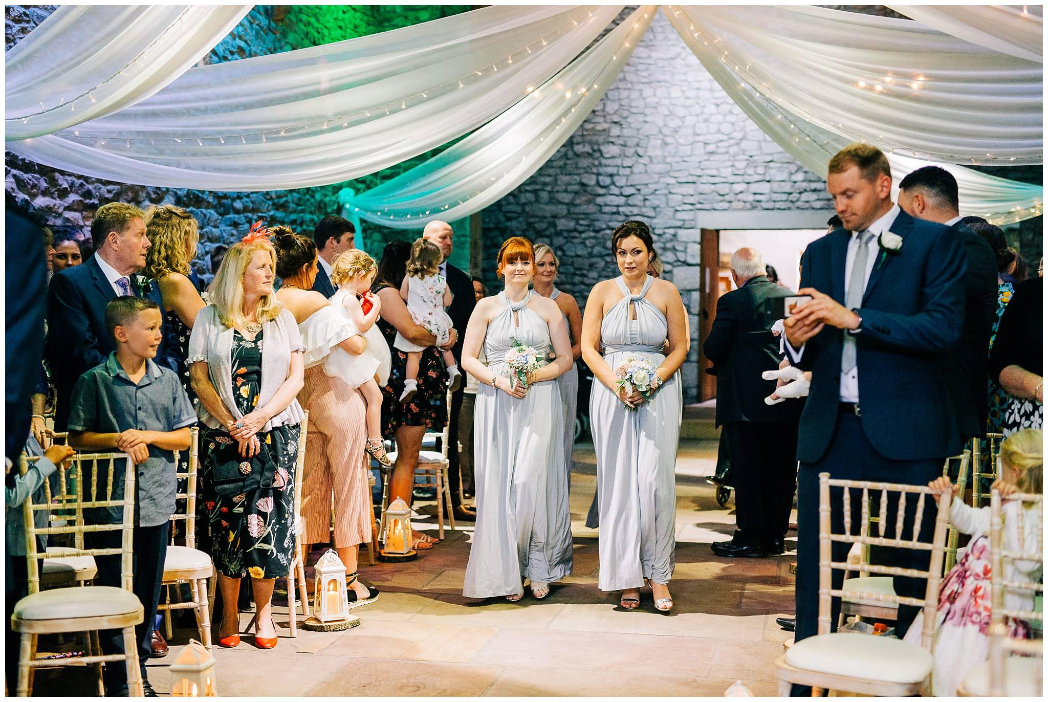 4 bridesmaids walking down the aisle at browsholme tithe barn