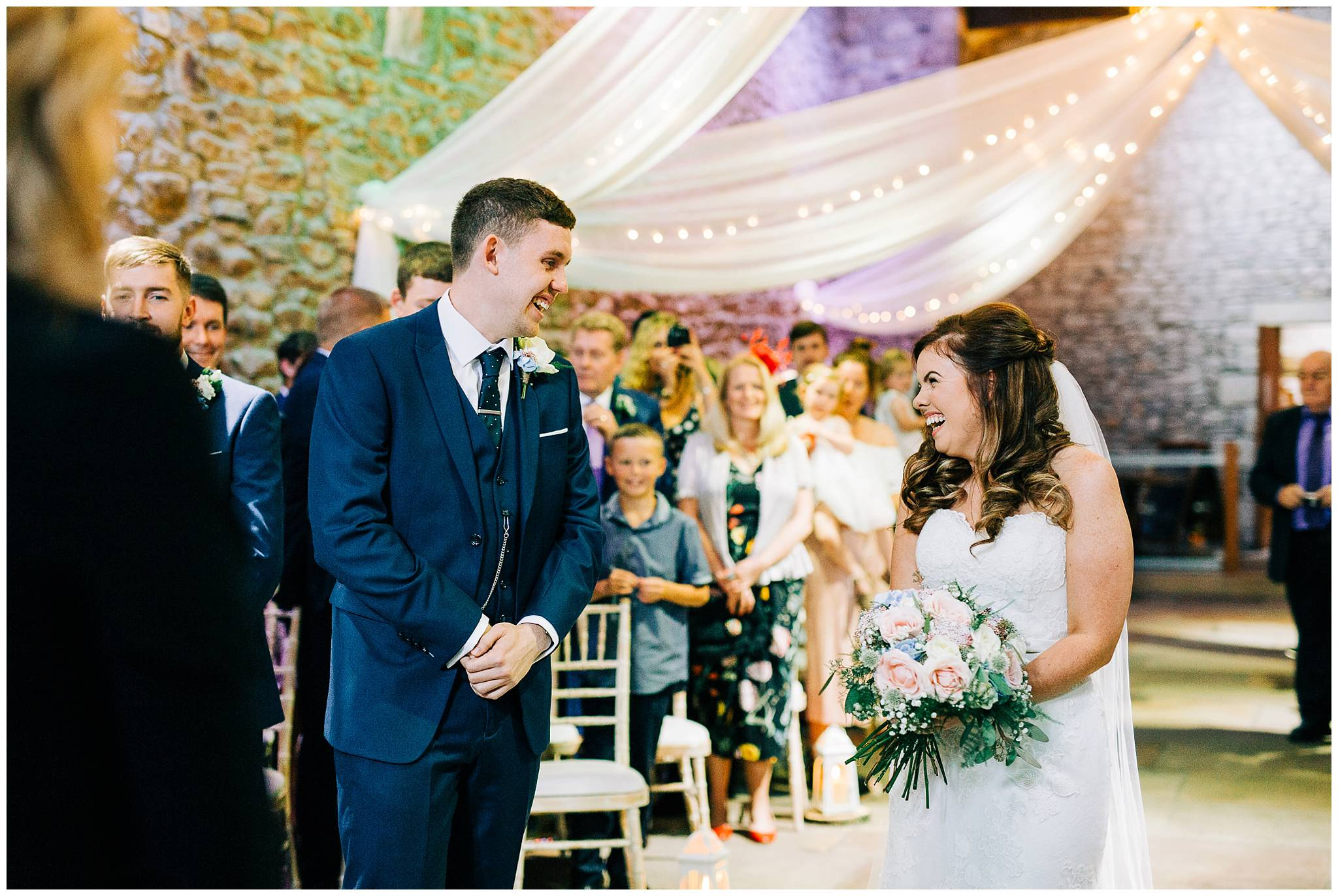 bride and groom smile at each other at the end of the aisle at browsholme hall tithe barn