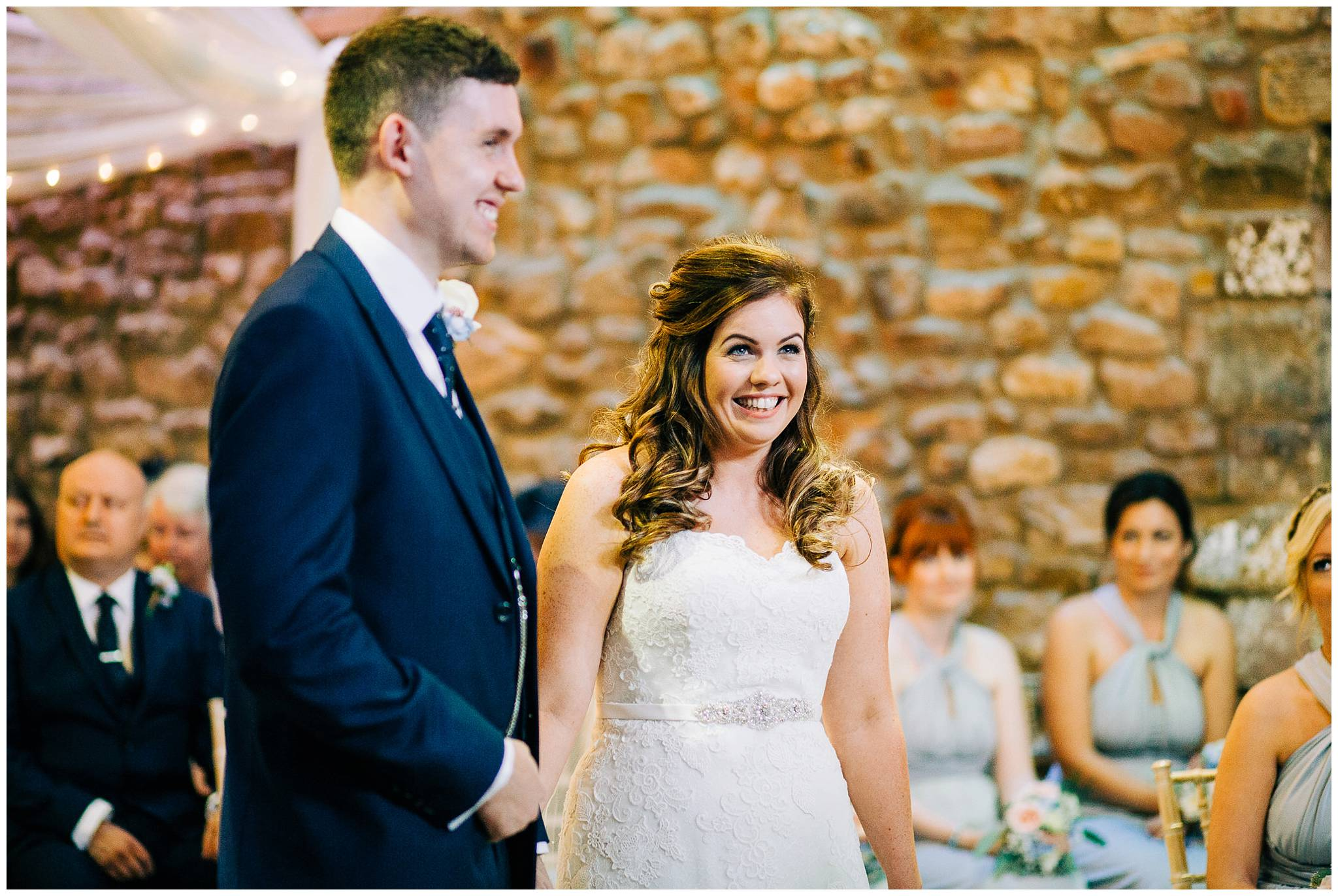 bride is excitedly smiling during ceremony at browsholme hall tithe barn