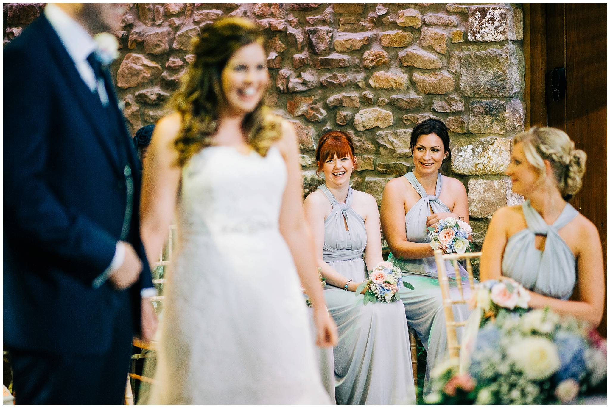 bridesmaids smiling at each other in the background during a ceremony at browsholme hall tithe barn