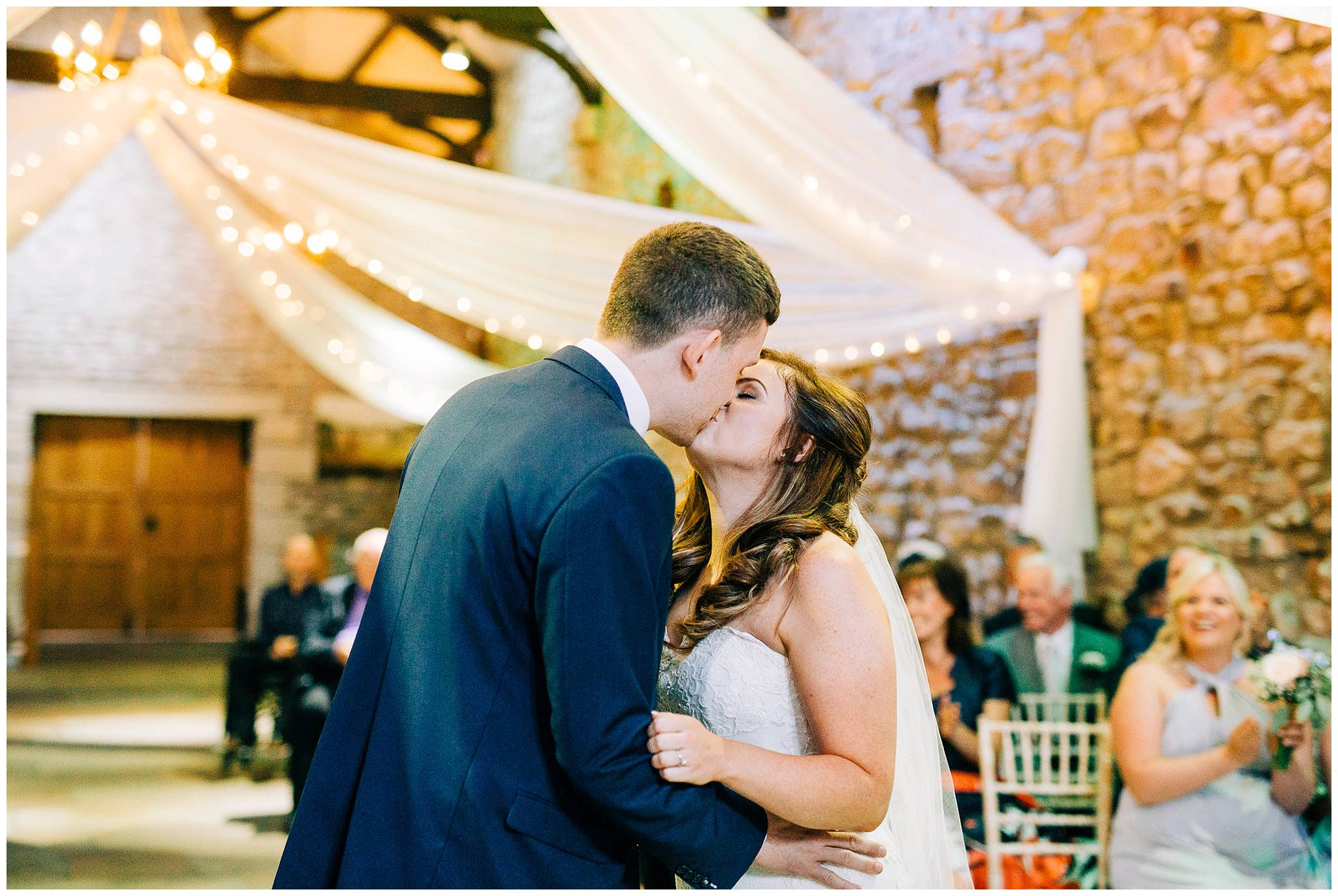 bride and grooms first kiss as mr and mrs at rustic barn venue browsholme hall tithe barn