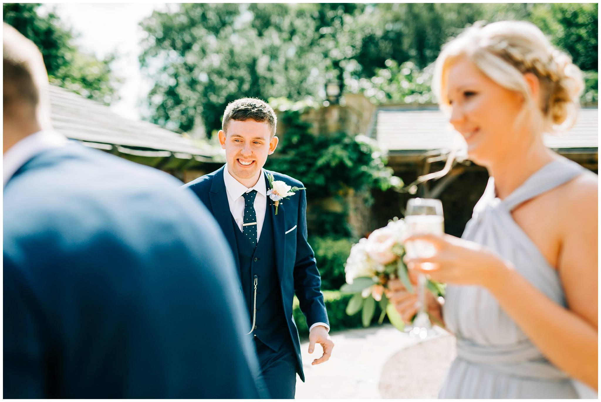 groom outside after ceremony smiling with guests