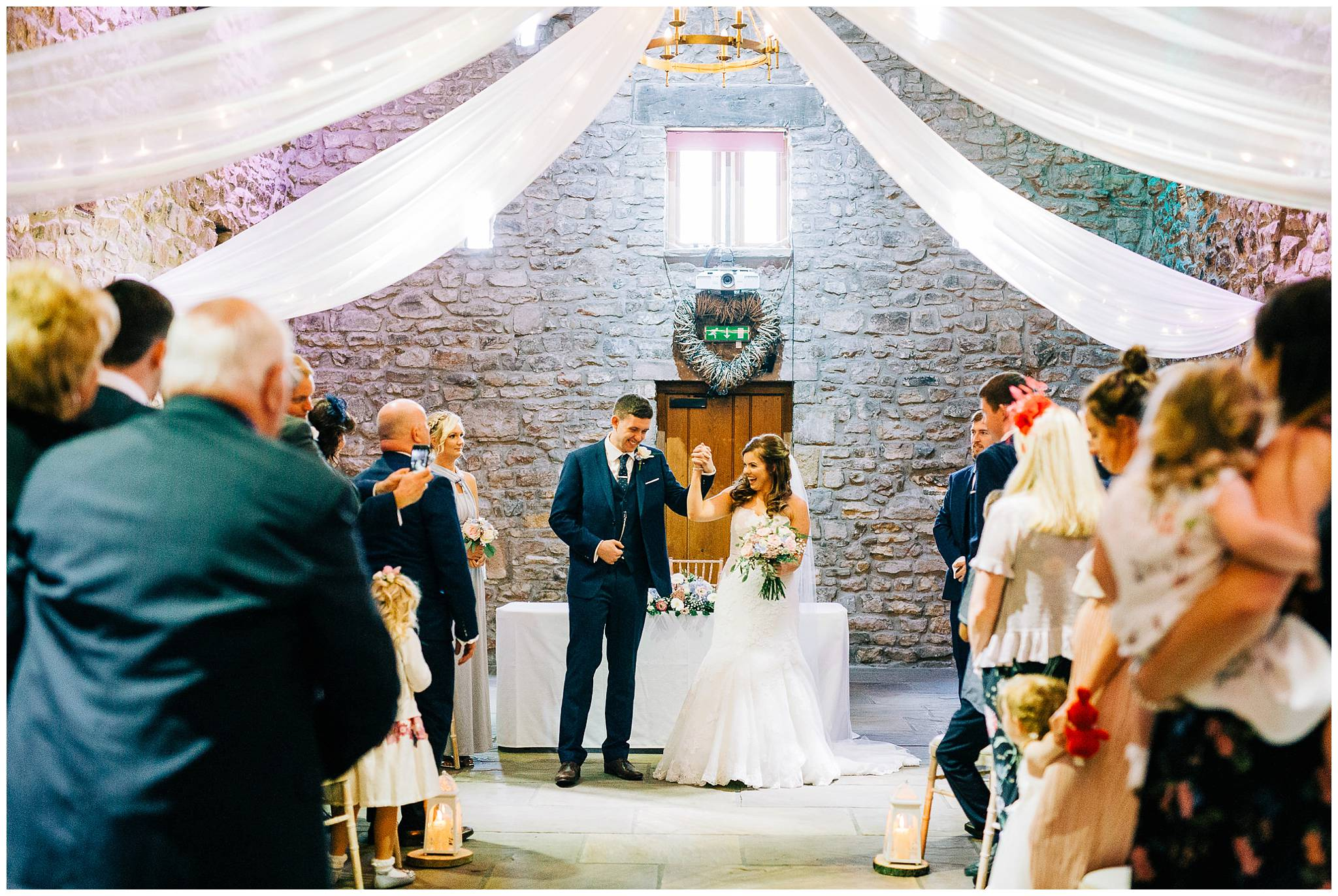 bride and groom punch air whilst holding hands after barn ceremony at browsholme hall titte barn