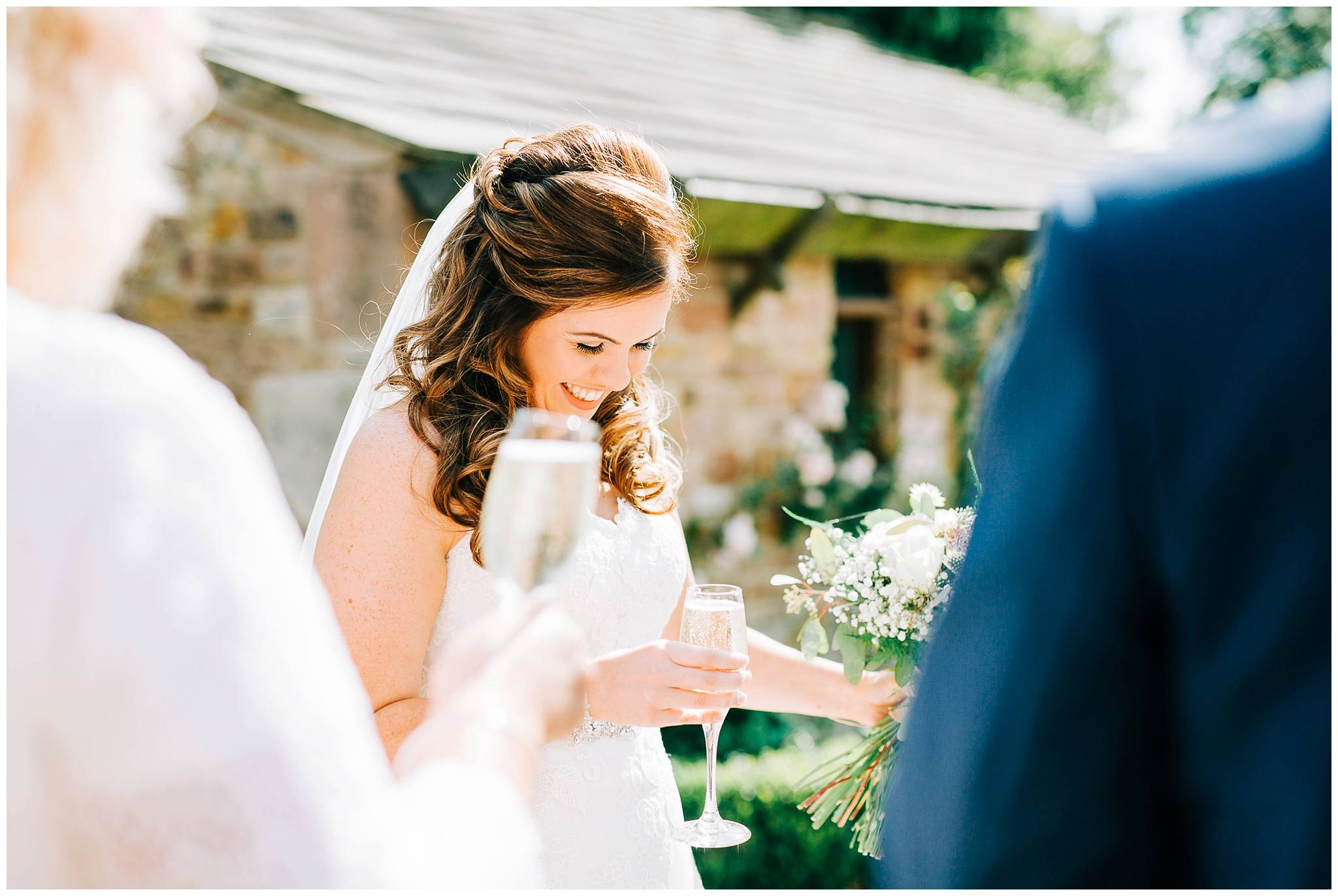bride smiling whilst holding glass of champagne outside oitside with guests