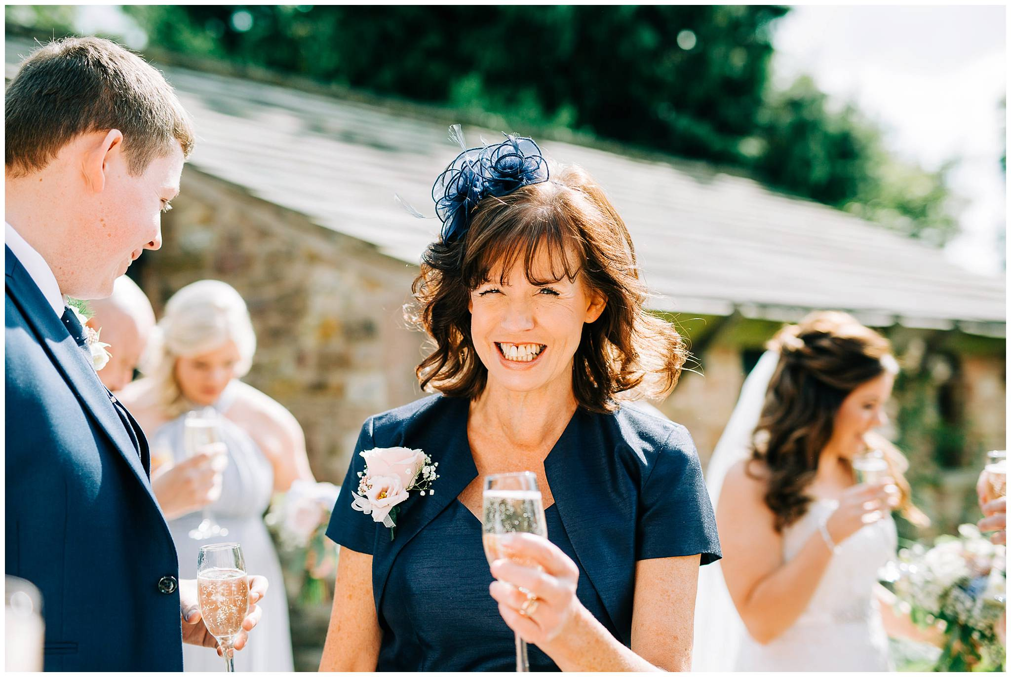 mother of the bride walking and smiling at the camera whilst holding a glass of champagne