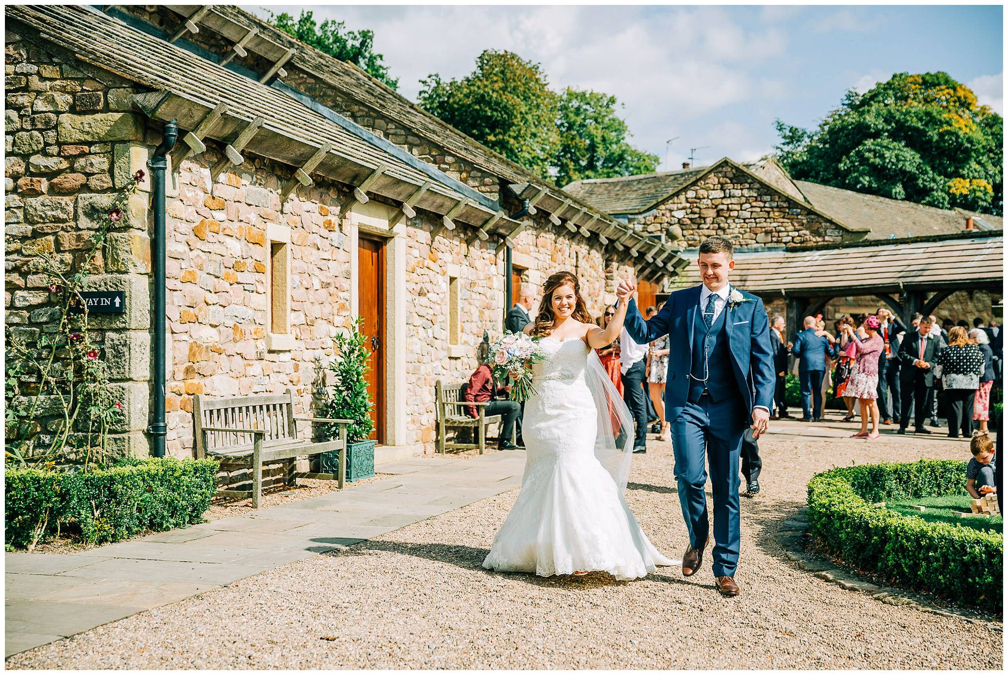 newlywed couple walking and punching the air whilst holding hands