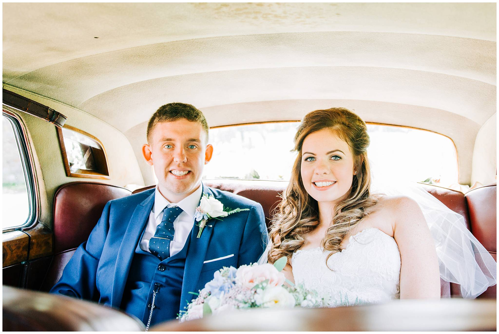 bride and groom sat in the back of a vintage bentley before having a drive