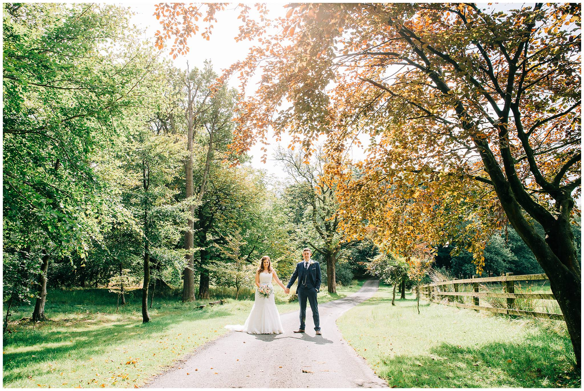 bride and groom stood in the middle of small rural road surround by grass and trees in the summer sunshine