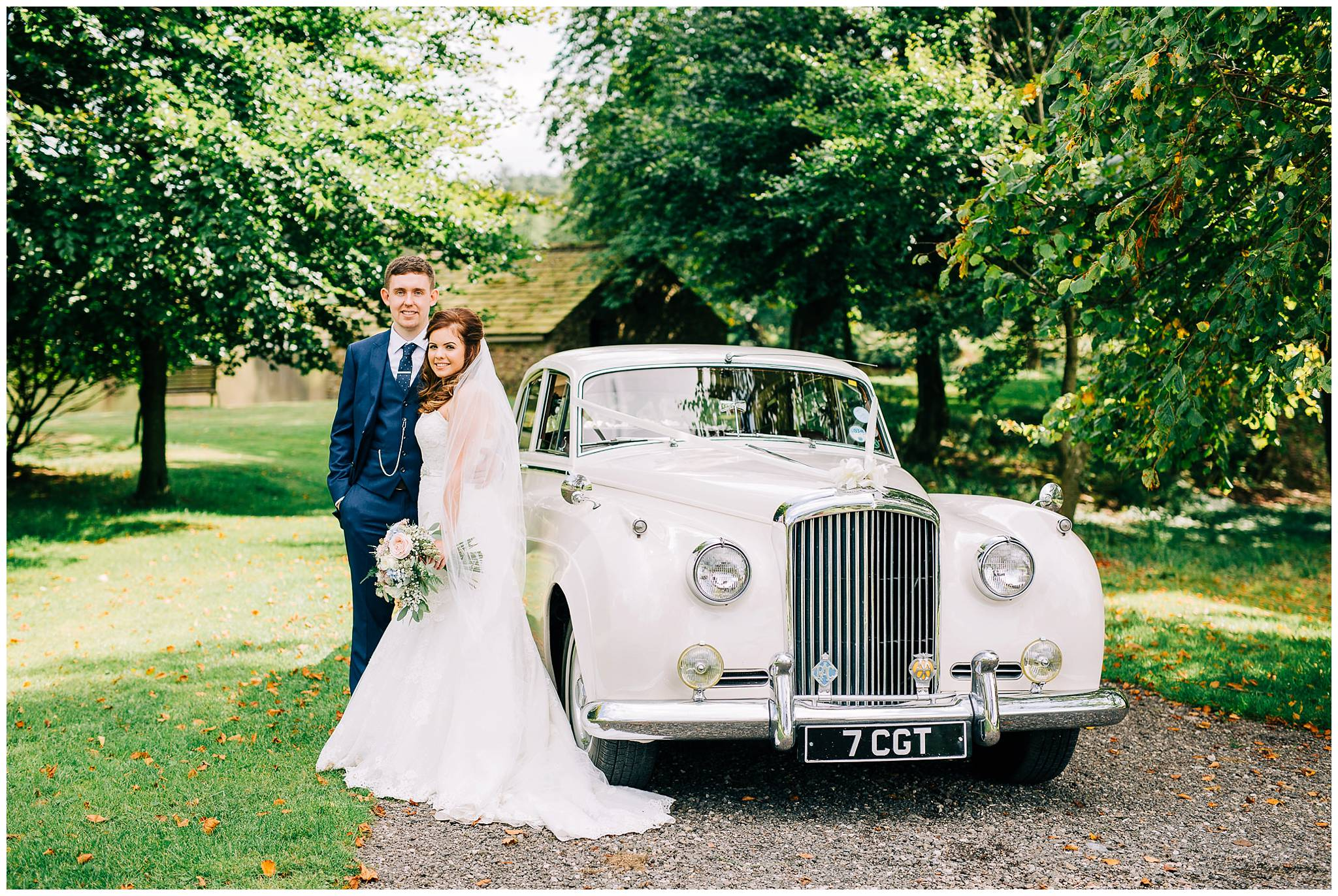 bride and groom stood at the side of vintage bentley with browsholme hall lake in the background